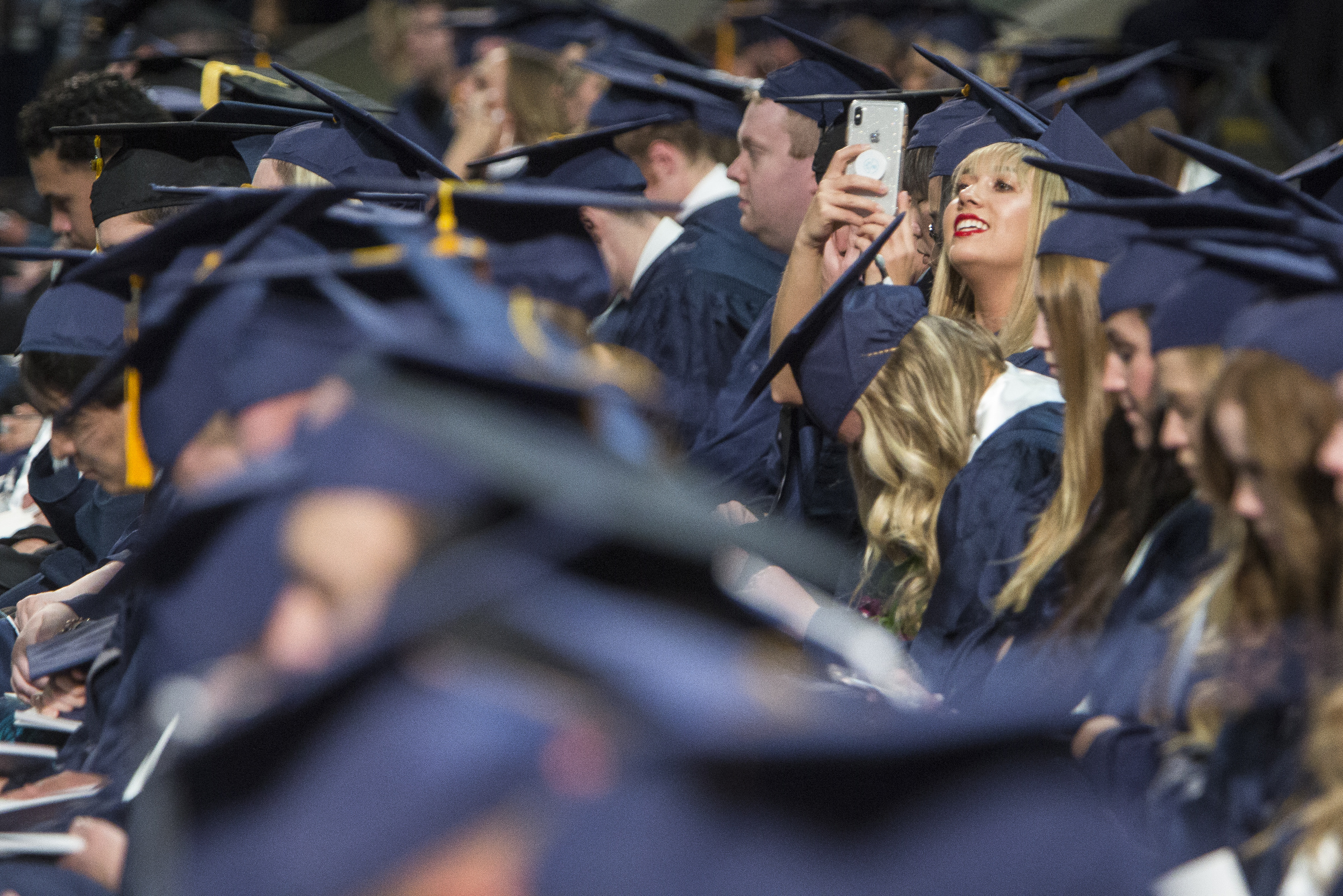 BYU graduate Chanel Kostich, of Rolling Hills Estates, California, uses her cell phone while attending Brigham Young University's commencement ceremony in the Marriott Center on Thursday, April 26, 2018, in Provo. BYU is awarding nearly 6,300 degrees to graduates this week.