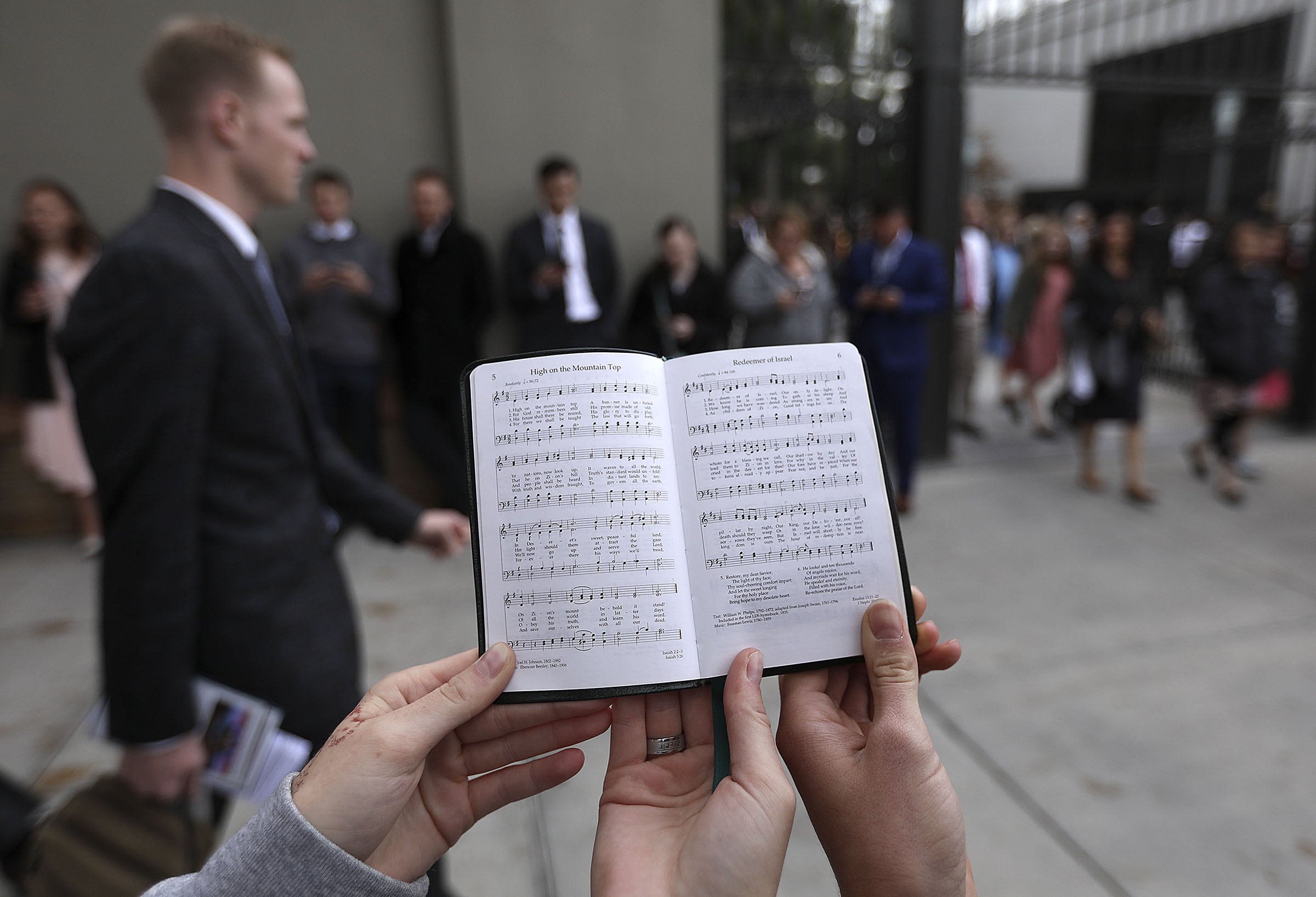Ryan Aust and Rebecca Sherrill sing hymns with other members of the Logan Young Single Adults First Stake between sessions of the 188th Semiannual General Conference of The Church of Jesus Christ of Latter-day Saints outside of Temple Square in downtown Salt Lake City on Sunday, Oct. 7, 2018.