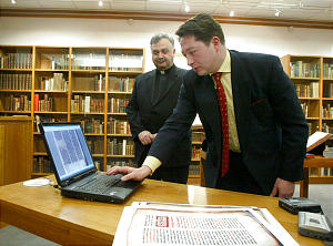 Kristian Heal of BYU demonstrates the DVD of ancient Syriac Christian documents digitized at the Vatican Library by BYU during a press conference at BYU's Harold B. Lee Library. Bishop Mar Bawai Soro of the Assyrian Church of the East in background. Bishop Soro contacted BYU with the DVD project. March 31, 2004. Photo by Stuart Johnson (Submission date: 03/31/2004)