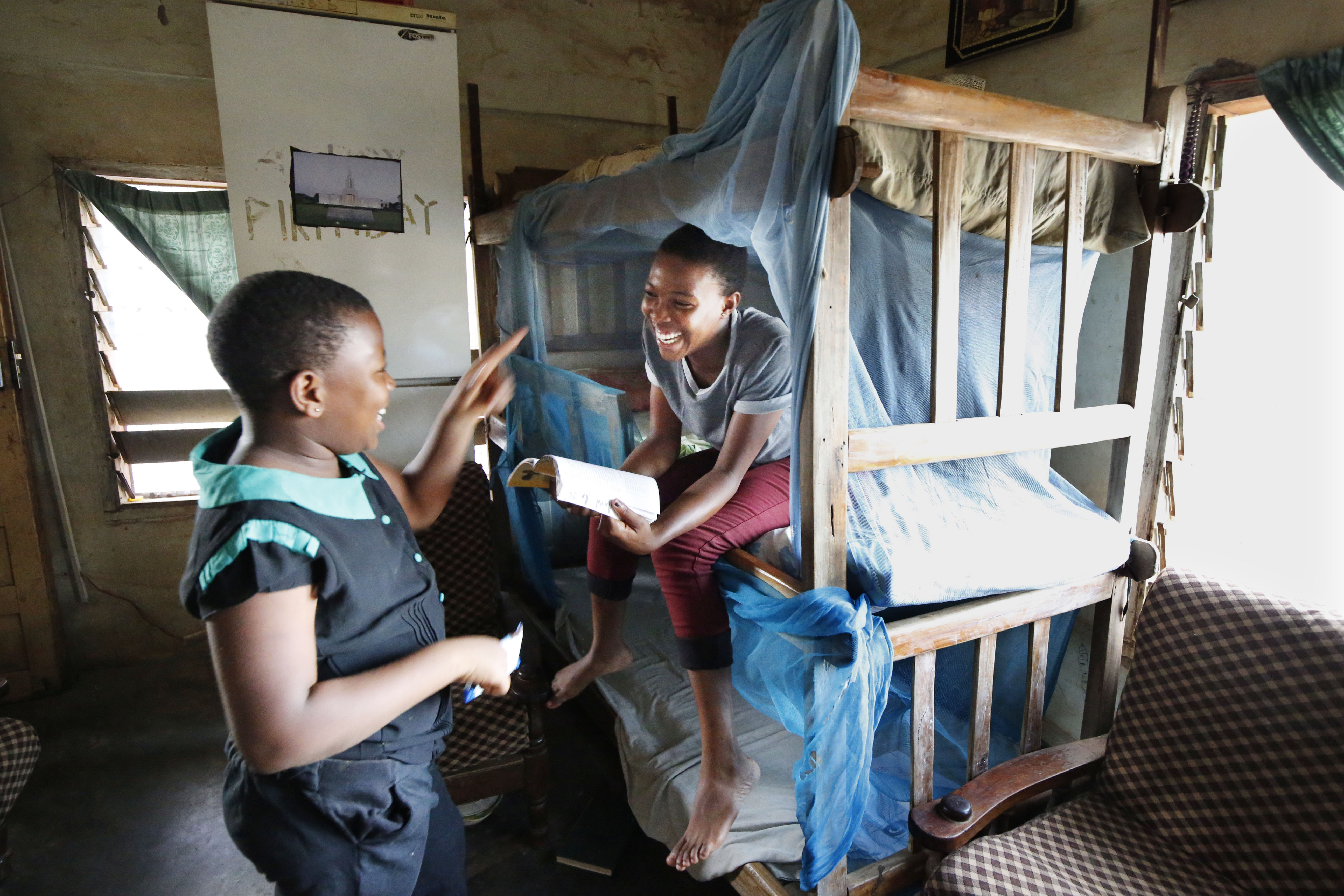 Dora, right, and Esther Samche joke with each other in the living room of their home in Kumasi, Ghana, on Saturday, April 21, 2018. Dora is sitting in her bed draped with mosquito netting.