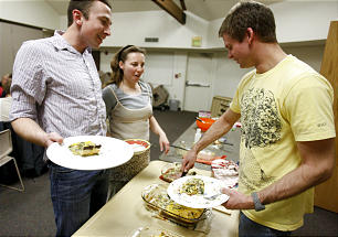 Gabriel Hess, left, Adeline Pichot and Michael Voge visit the buffet for dinner in the French House.