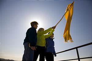Young Women general presidency, from left, Mary N. Cook, first counselor, Elaine S. Dalton, president, and Ann M. Dibb, second counselor, stand atop Ensign Peak waving a banner.