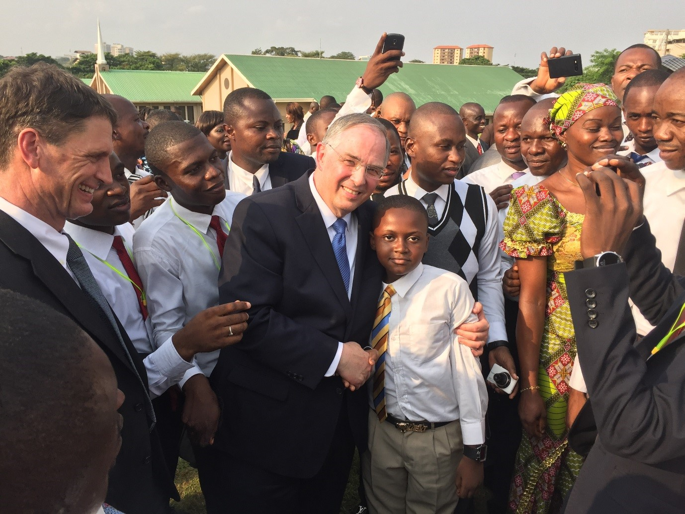 Elder Neil L. Andersen greets members attending the groundbreaking for the Kinshasa Democratic Republic of the Congo Temple on Friday, February 12, 2016.