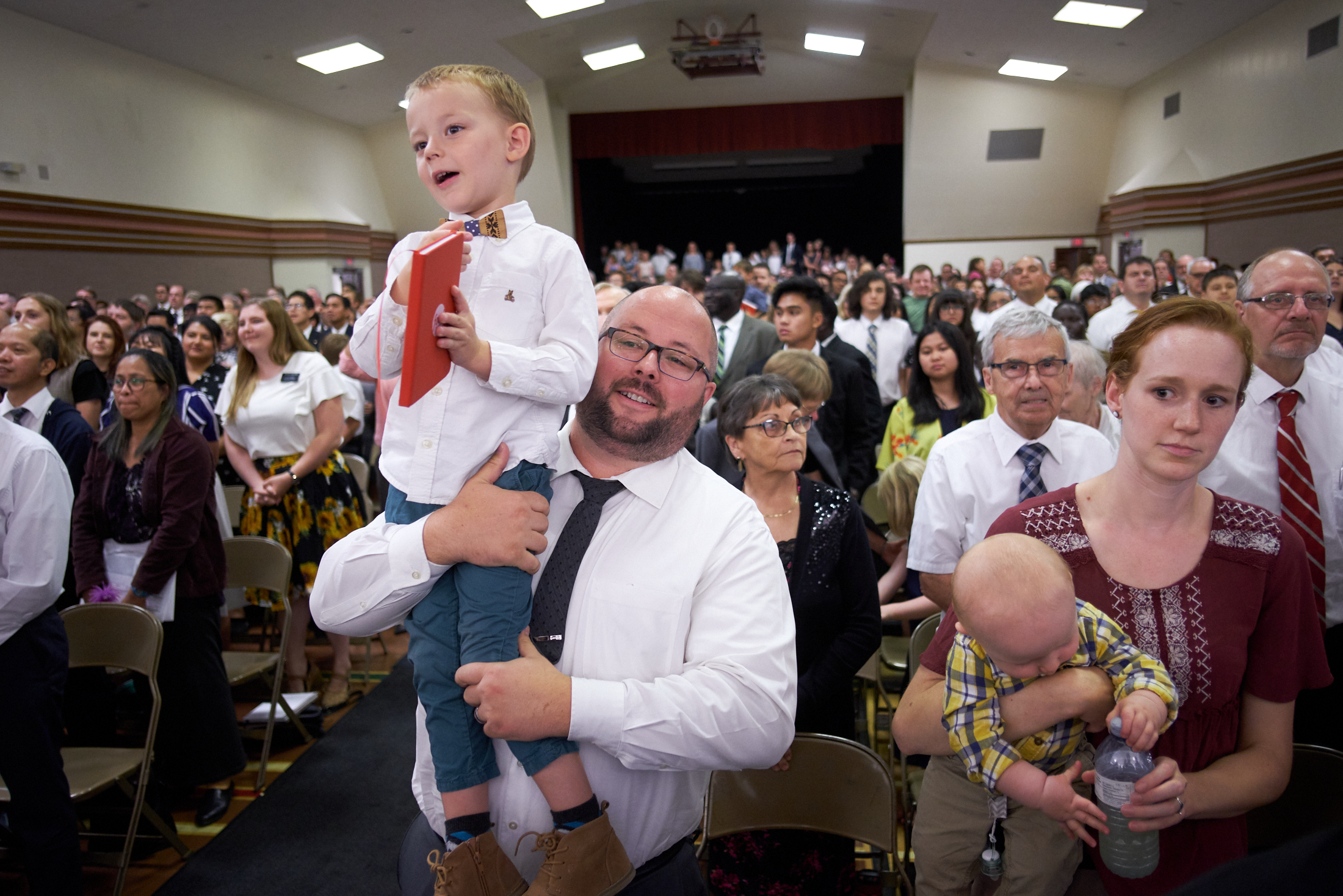 A man holds up his son to see the prophet during a devotional with President Russell M. Nelson and his wife, Sister Wendy Nelson, in Winnipeg, Manitoba, on Friday, Aug. 17, 2018.