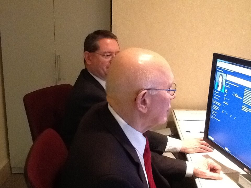 """In a May 27, 2015, Facebook post, then-Elder Dallin H. Oaks works with Dwayne Saviano at a missionary assignment meeting. """"I assigned 240, my share of the 1,047 (which includes young missionaries, senior couples, and senior sisters) whose papers were ready for assignment last week. We are assisted in this sacred experience by a member of the Missionary Department staff, who keeps records and manages the computer screens on which we view the essential information on elders and sisters and the needs (including languages) of our more than 400 missions in the world."""""""