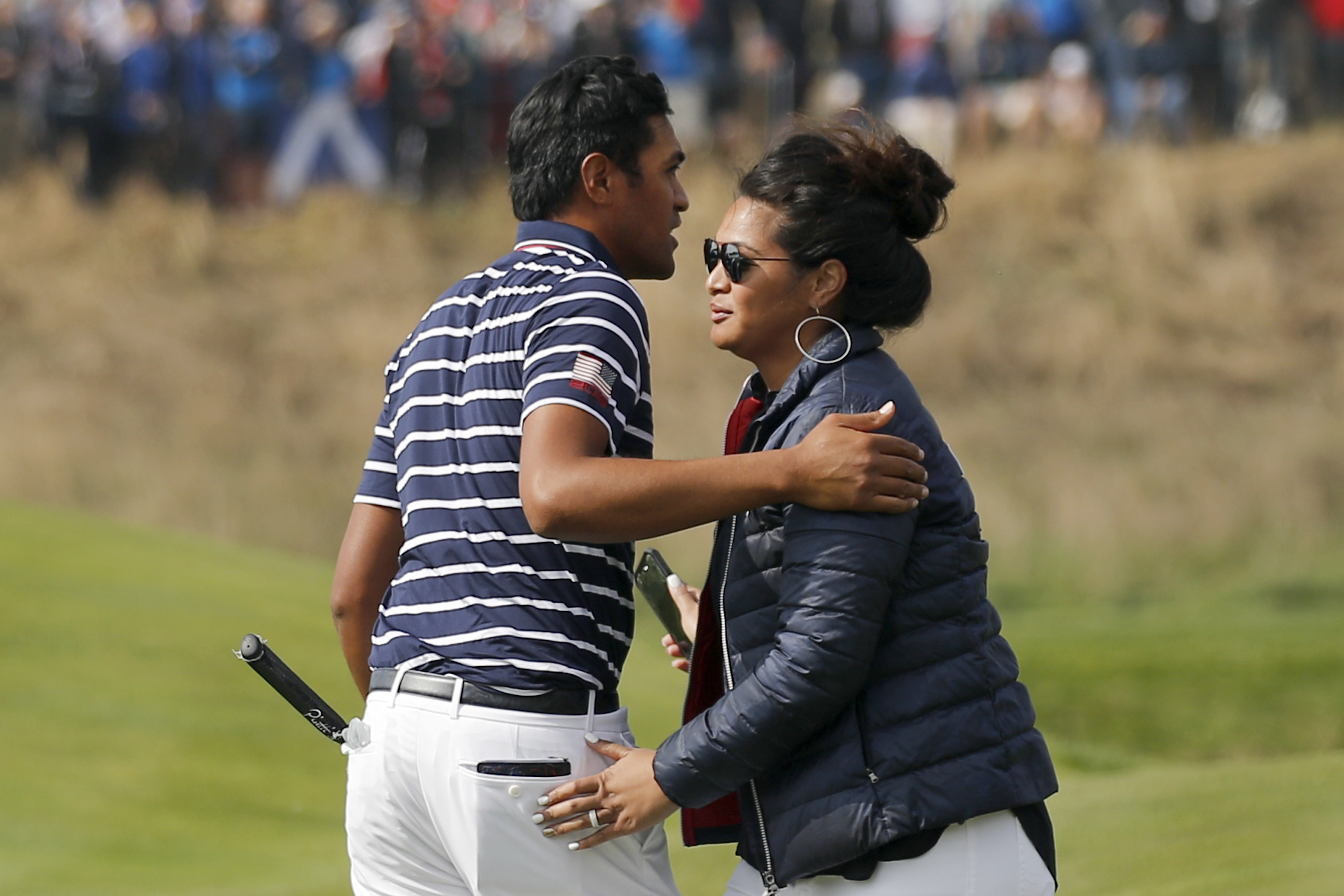 Tony Finau is congratulated by his wife, Alayna Galea'i-Finau, after winning his fourball match with his teammate Brooks Koepka on the opening day of the 42nd Ryder Cup at Le Golf National in Saint-Quentin-en-Yvelines, outside Paris, France, Friday, Sept. 28, 2018.