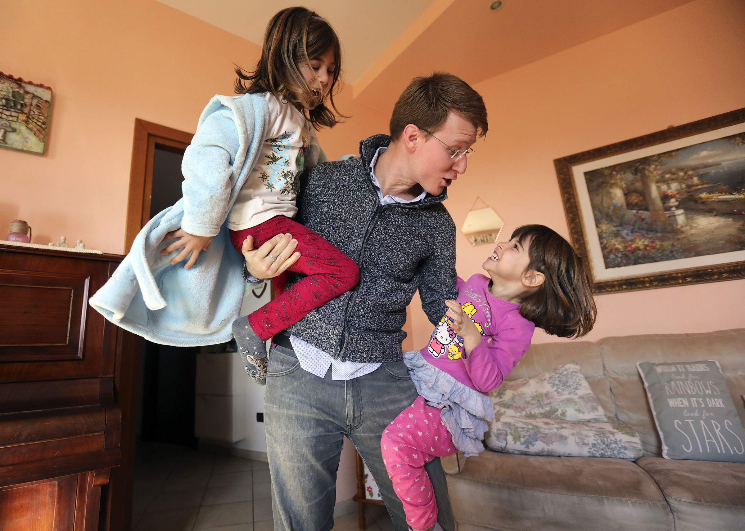 Daniele Salerno plays with his daughters Emma, left, and Alice, right, at home in Rome, Italy, on Sunday morning, Nov. 18, 2018.