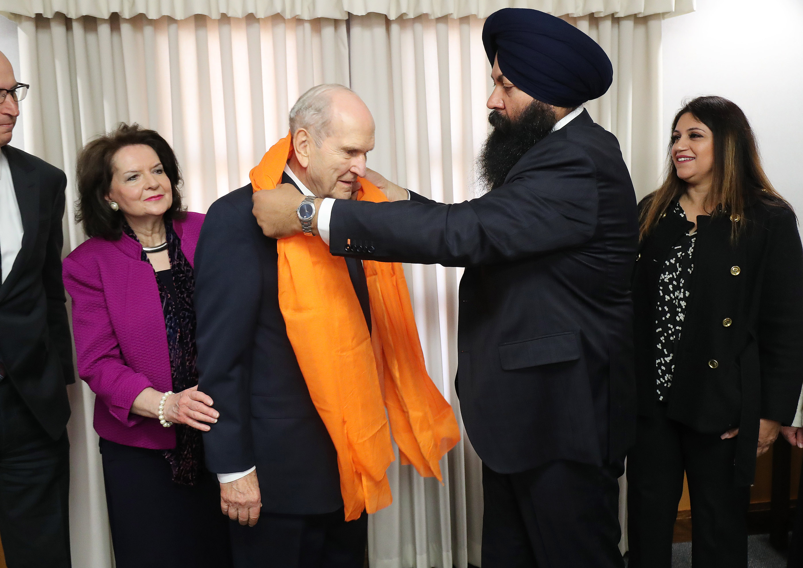 President Russell M. Nelson of The Church of Jesus Christ of Latter-day Saints is honored with a Saropah from Sikh leader Karmdeep Bains in Chico, California, on Sunday, Jan. 13, 2019, two months after the Camp Fire destroyed more than 18,000 homes and businesses. Sister Wendy Nelson, left, and Harpreet Bians look on.