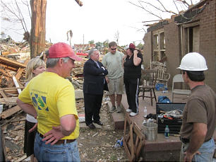 Area Seventy Elder R. Randall Bluth speaks with Colleen Robbins and other members outside the ruins of the Robbins home.