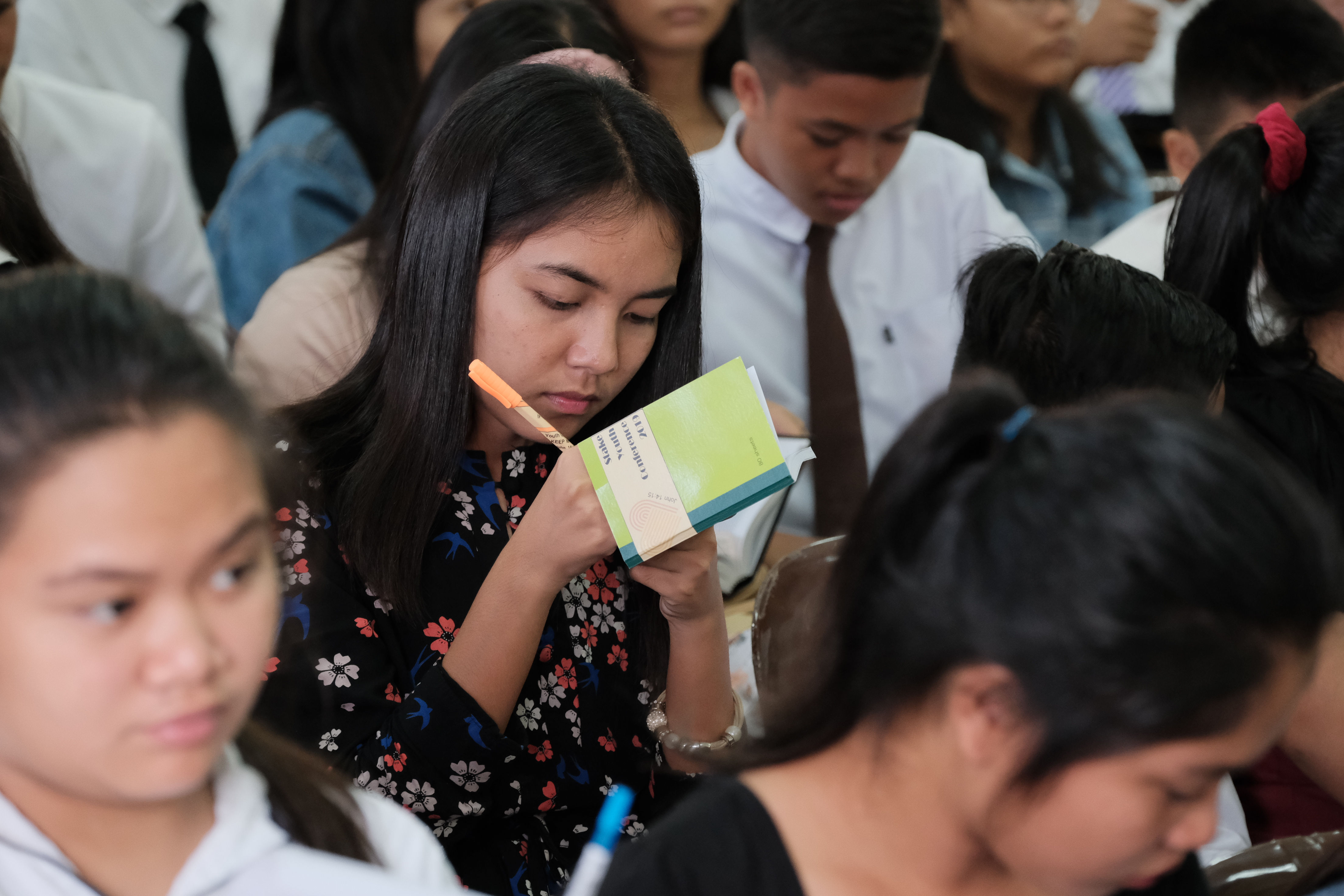 Youth members take notes during a devotional with Elder Dale G. Renlund in Bacolod, Philippines, during his recent visit to the island nation.