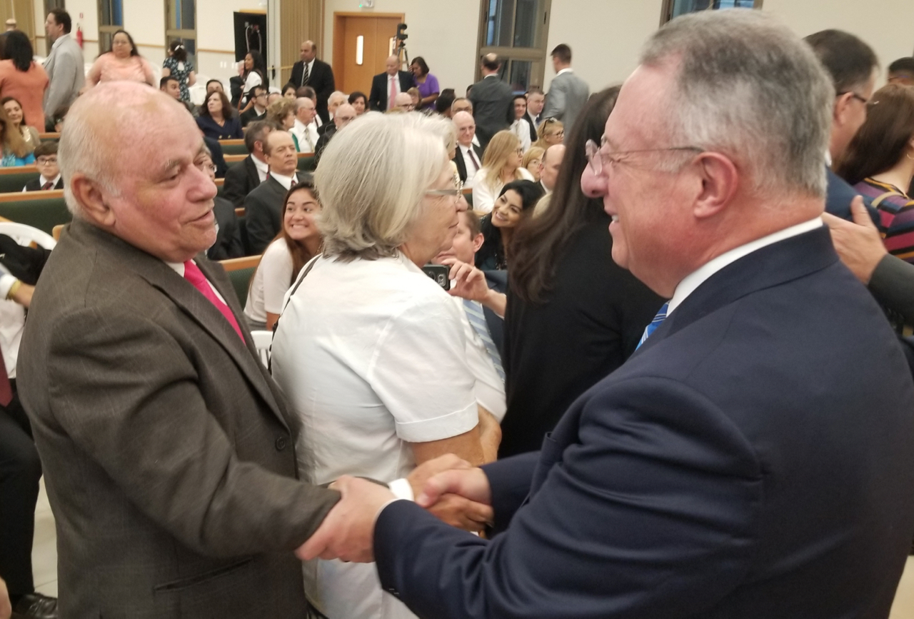 Elder Ulisses Soares of the Quorum of the Twelve Apostles, right, greets Antonio Ferreira following a meeting with visiting Church leaders and the pioneer members of Fortaleza, Brazil, on June 1, 2019.