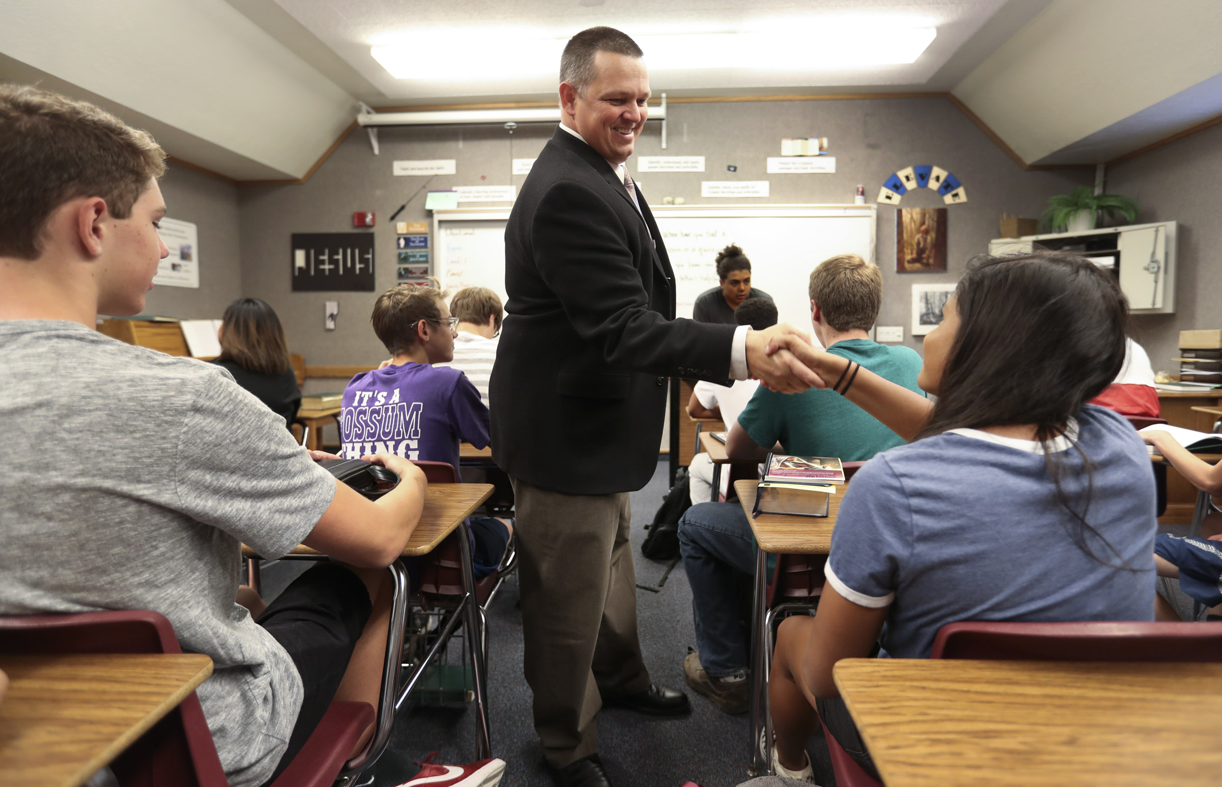 West High's Seminary principal, Trent Smith, shakes hands with his students at the start of his LDS seminary class at West High School in Salt Lake City on Monday, Sept. 17, 2018.