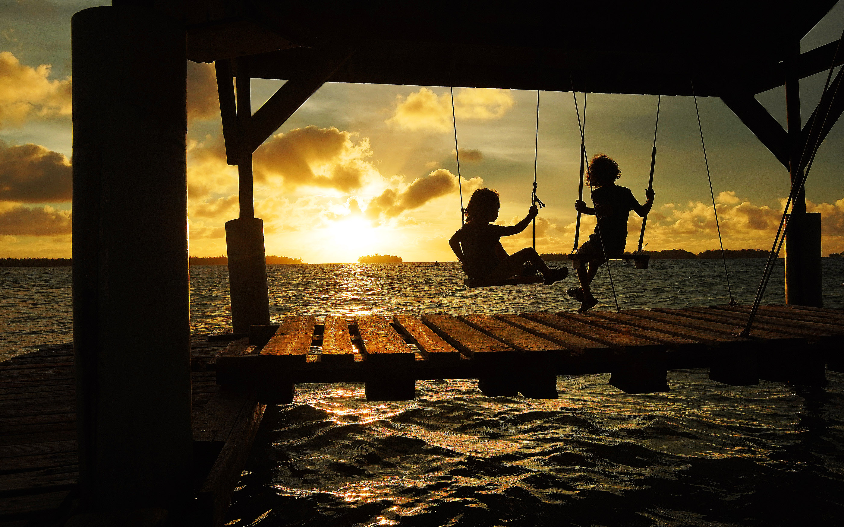 Kids play on swings as the sun sets in Bora Bora on May 27, 2019.