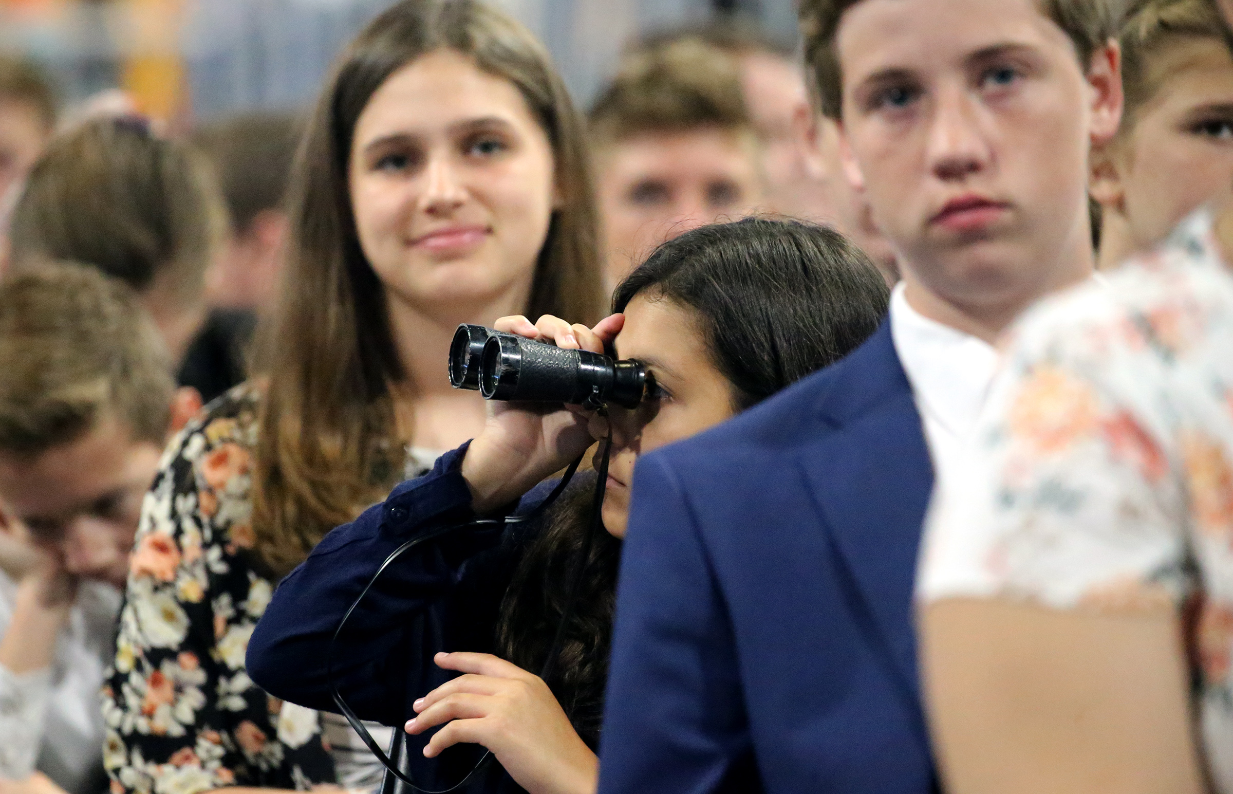 A young woman uses a pair of binoculars to look around the arena at a devotional with President Russell M. Nelson and others at the Amway Center in Orlando, Florida, on Sunday, June 9, 2019.