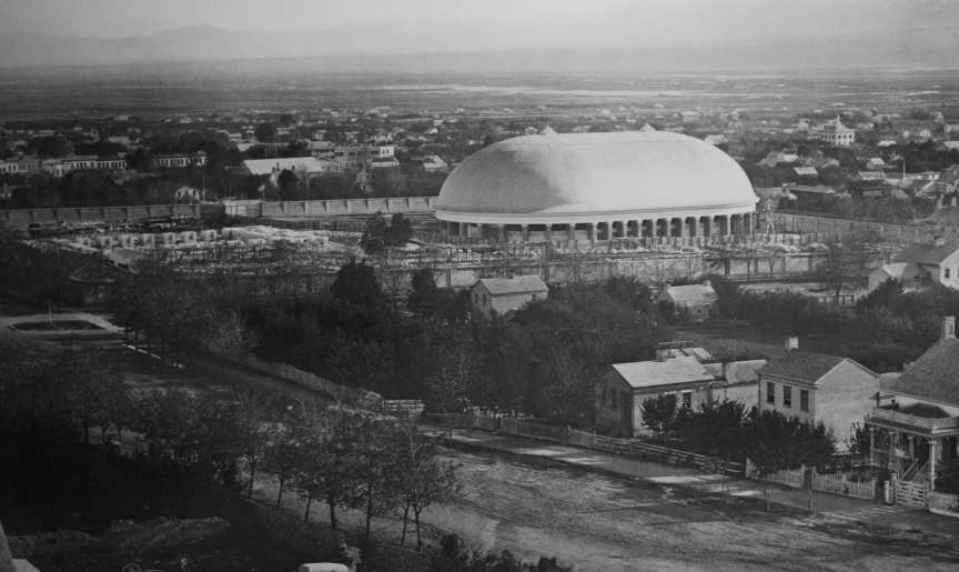 This historical photo shows the Salt Lake Tabernacle with the foundation of the Salt Lake Temple to the left.