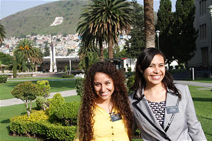 """Sister Tania Hernandez, left, and Sister Eva Lima stand outside the entrance of the Mexico City MTC. The """"B"""" placed prominently on the mountainside remains a nod to the campus' rich Benemerito history."""