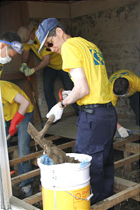 Sendai Mission President Reid Tateoka of Holladay, Utah, shovels sludge from low income housing during missionary service project.