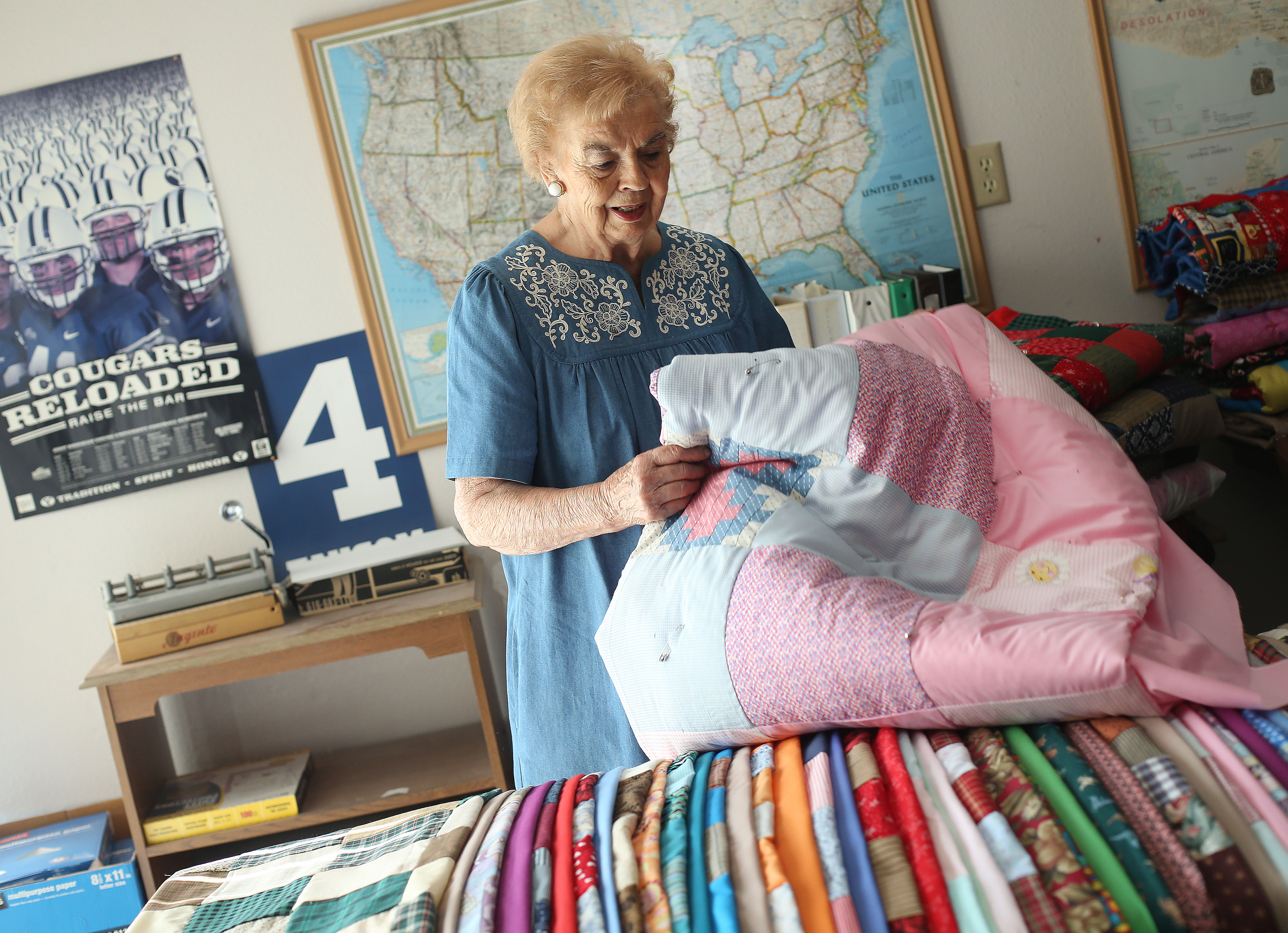 Joyce Nixon sorts through some of her quilts in her Orem home on Wednesday, July 10, 2019. Nixon has made more than 2,700 quilts for charity.
