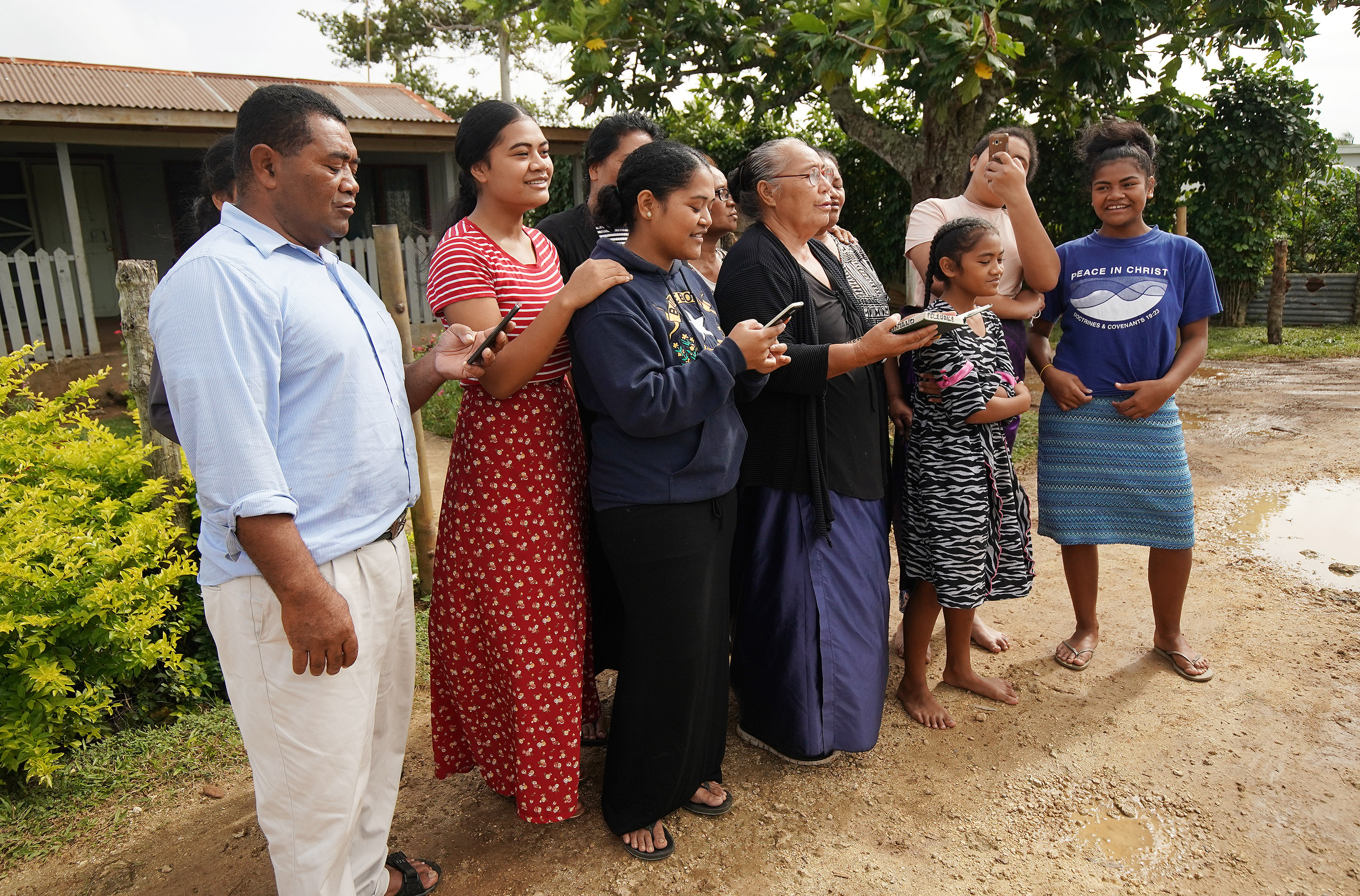 Tohiminiti Latu and his wife Ana sing a hymn with some of their children and neighbor outside their home in Tonga on May 23, 2019. Latu is bishop of his ward and has 10 children and one grandchild.