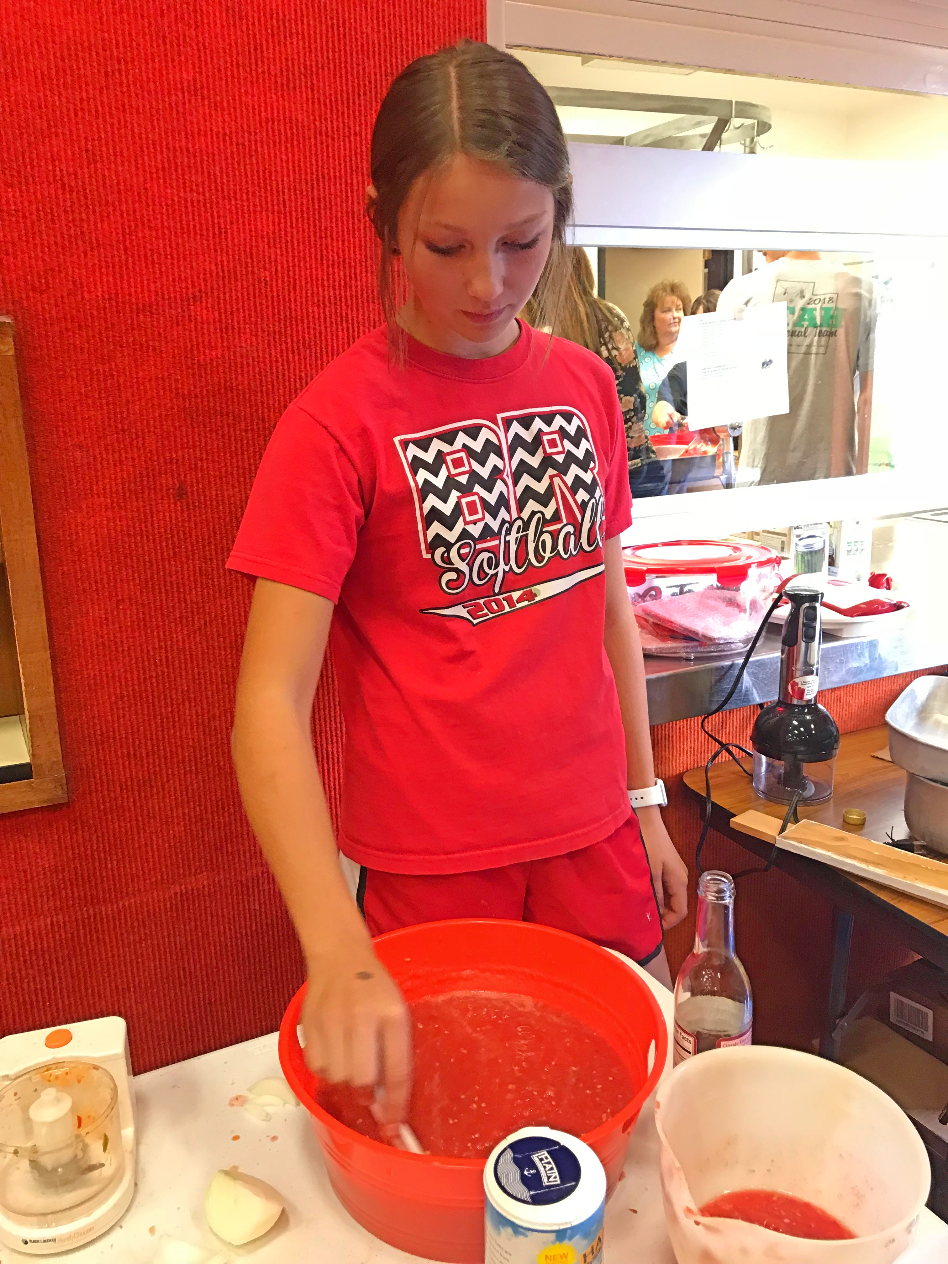 Baylee Sorensen stirs a bowl of salsa before it's canned during a youth canning activity at the Howell Community Center on Saturday, Sept. 8, 2018.
