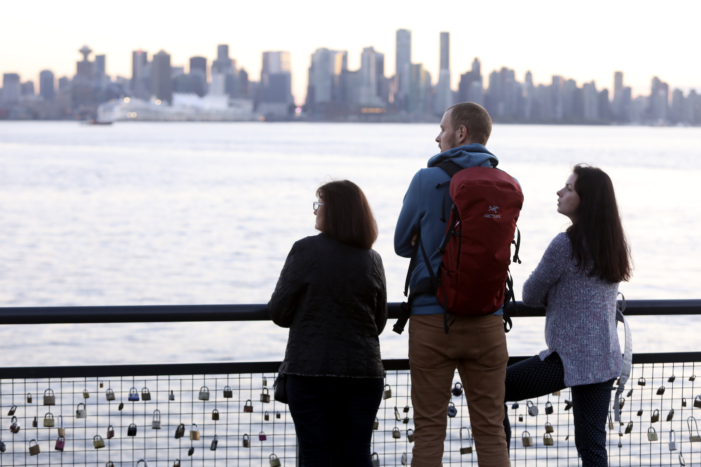 Olga Boiko, Pavel Boiko and Daria Boiko look out at the Vancouver skyline from Lonsdale Quay in North Vancouver, British Columbia, on Monday, Sept. 17, 2018.