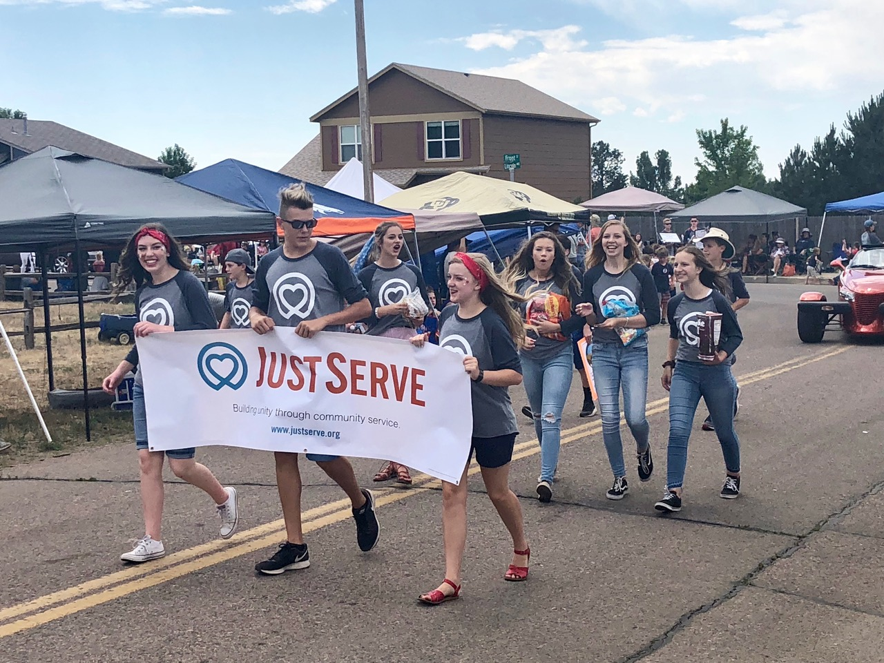 Several youth from the Colorado Springs North Stake represent JustServe during the Monument Hill Kiwanis parade in Monument, Colorado.