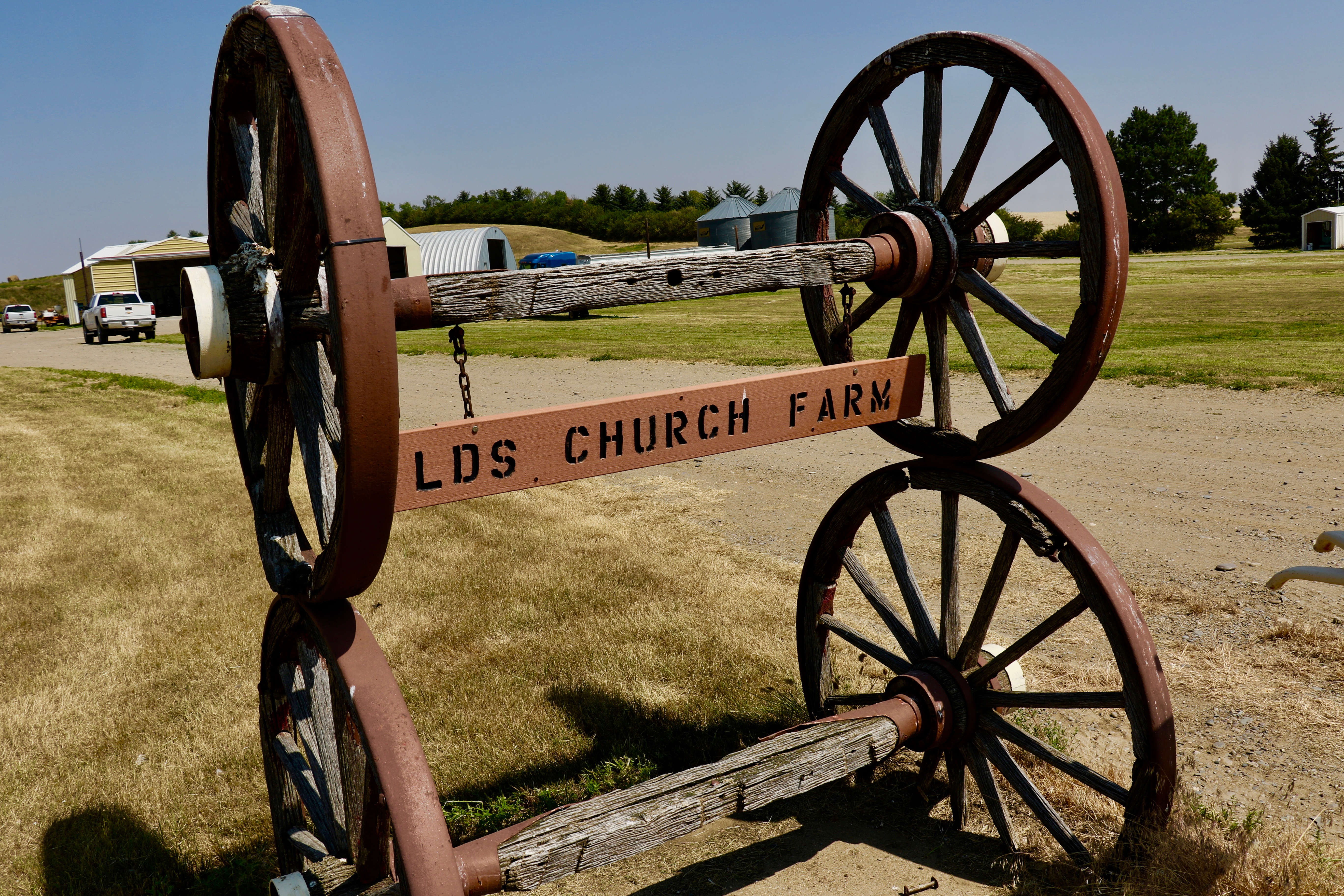 Rustic wagon wheel sign welcomes visitors to the Church-owned Geraldine Montana Crops welfare farm in northwest Montana. Despite ongoing drought parching the Western United States, the Montana farms expects an abundant wheat crop in 2021.