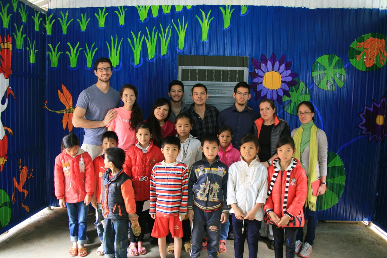 Members of Gerrit W. Gong's family stand in front of mural project with the children who assisted them in Vietnam.