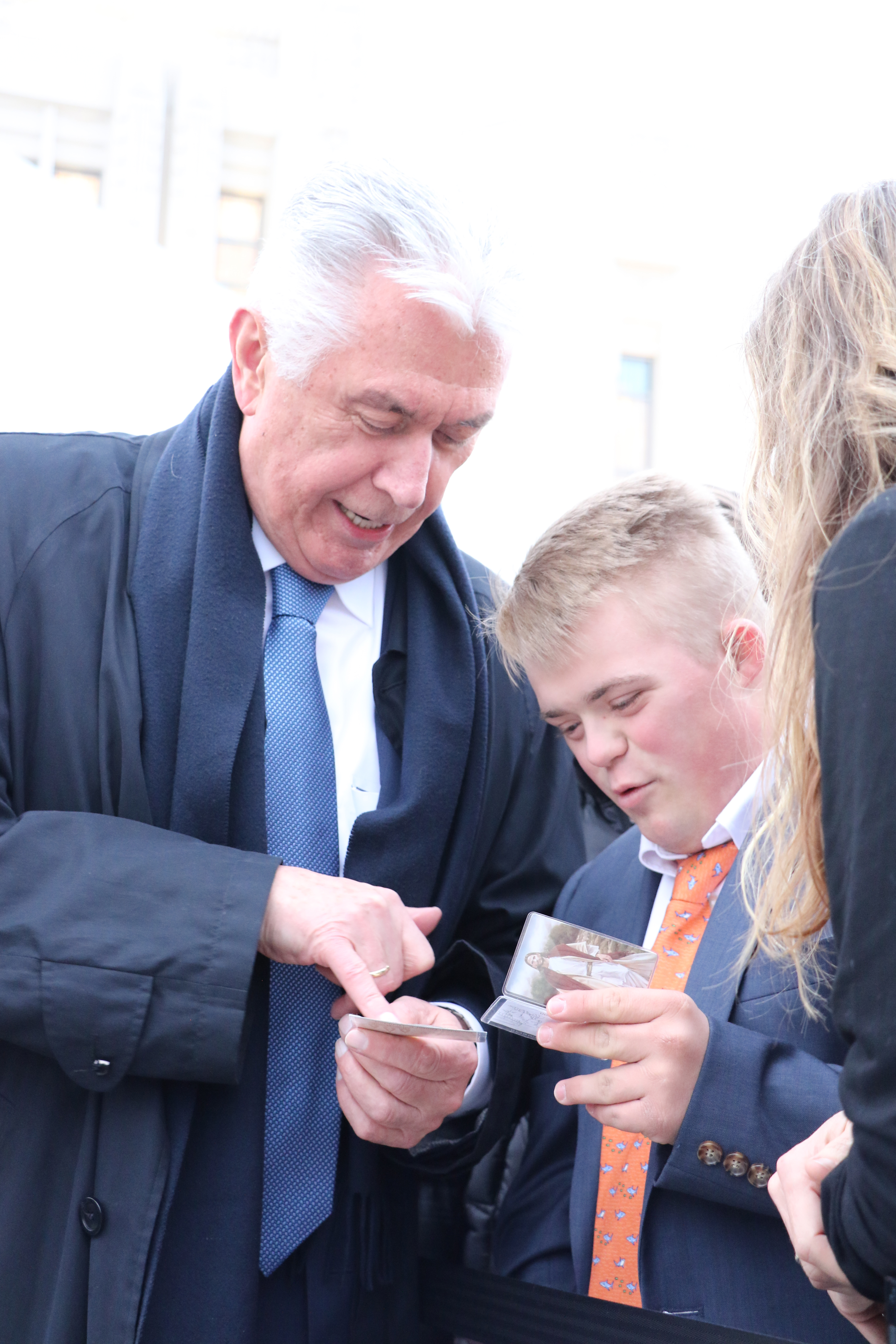 A young man shows President Dieter F. Uchtdorf his temple recommend.