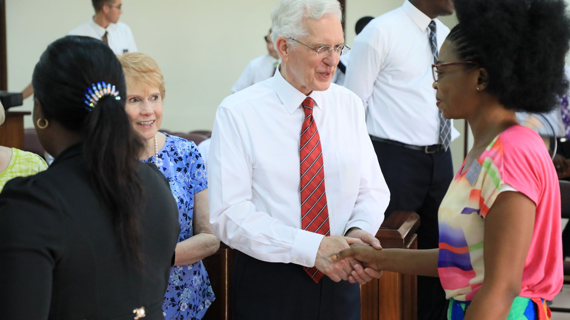 Elder D. Todd Christofferson and Sister Kathy Christofferson greet Relief Society sisters during a gathering in Cote d'Ivoire.