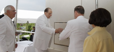 President Thomas S. Monson passes trowel to Elder Jeffery R. Holland during the ceremony to seal the symbolic cornerstone of Kansas City Missouri Temple. Elder William R. Walker of the Seventy is on the left, Sister Patrica Holland, is at the right.