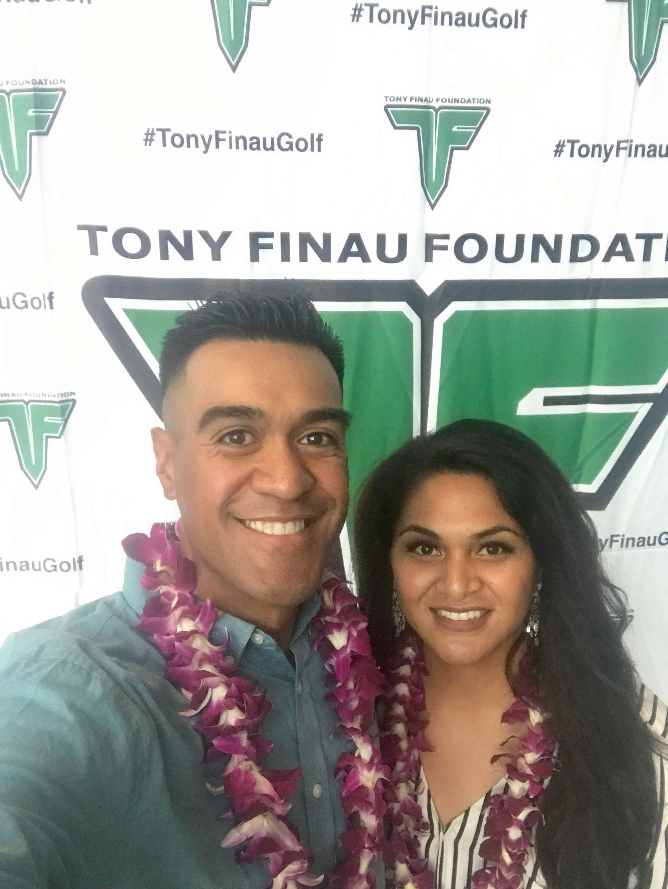 Tony Finau and Alayna Finau pose for a photo by a Tony Finau Foundation backdrop.