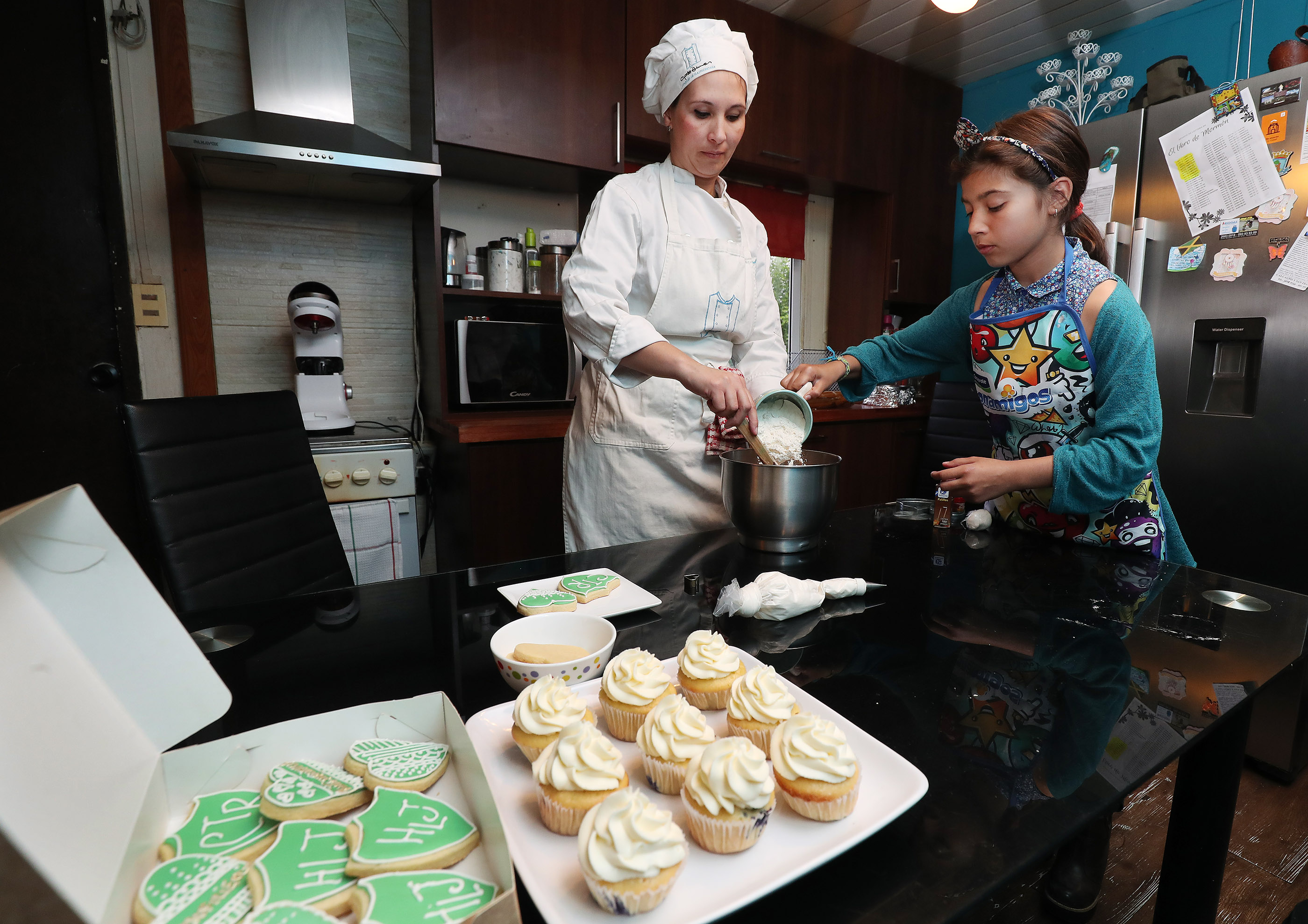 Janaina Silva Molla gets help from her daughter Sofia as she bakes at home in Montevideo, Uruguay, on Thursday, Oct. 25, 2018. Molla is building a business to supply cakes and pastries for parties with skills acquired by Self Reliance classes offered by the Church.