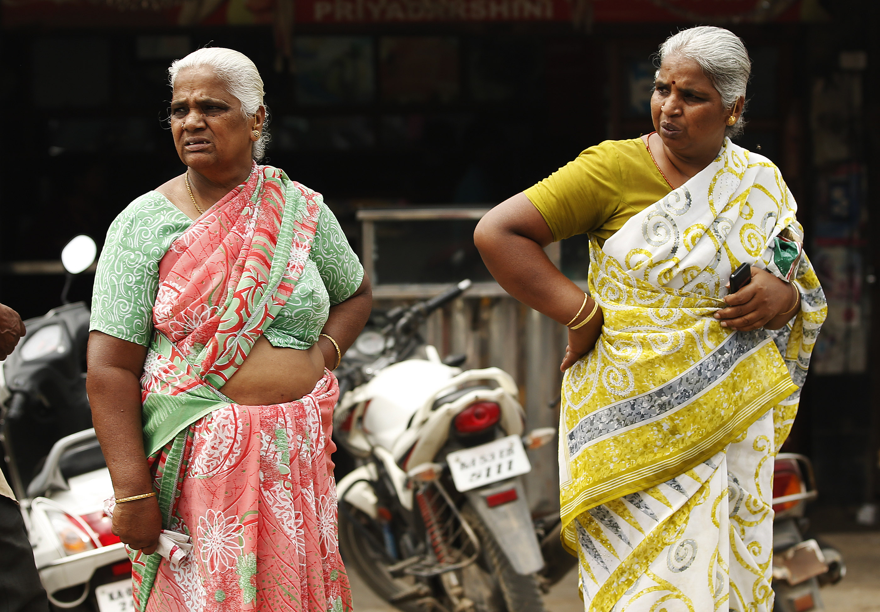 Two women stand on the street in Bengaluru, India, on Thursday, April 19, 2018.