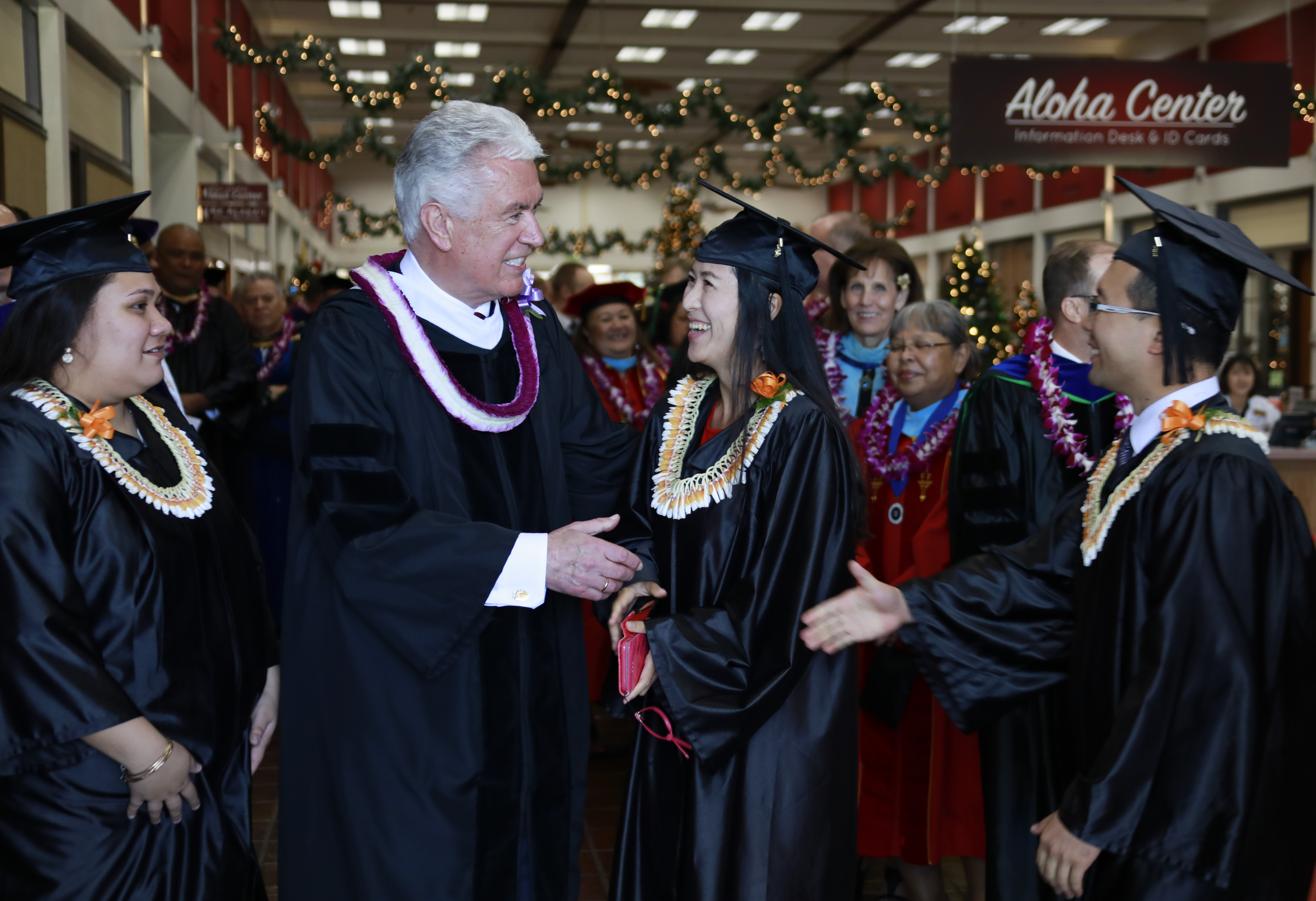 Elder Dieter F. Uchtdorf of the Quorum of the Twelve Apostles greets BYU-Hawaii graduates after giving the commencement address on Dec. 14.