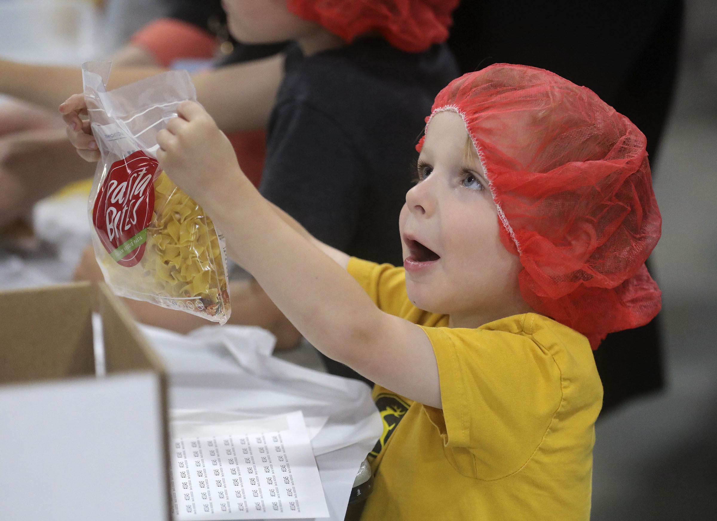 Rhett Thueson helps bag pasta dinners for a service project during the 68th United Nations Civil Society Conference at the Salt Palace Convention Center in Salt Lake City on Monday, Aug. 26, 2019.