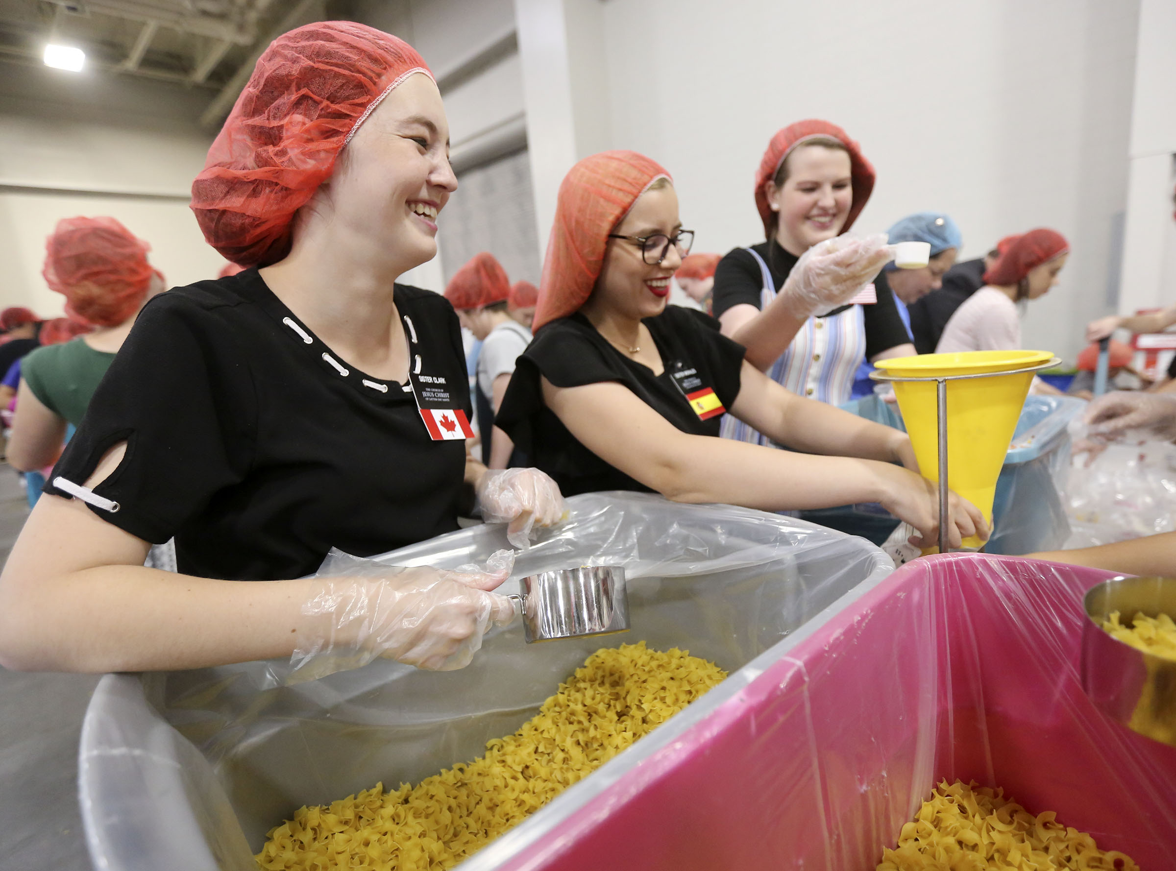 Temple Square missionaries Sister Zoey Clark, Sister Priscilla Morales and Sister Callie Jorgensen package pasta dinners for a service project during the 68th United Nations Civil Society Conference at the Salt Palace Convention Center in Salt Lake City on Monday, Aug. 26, 2019.