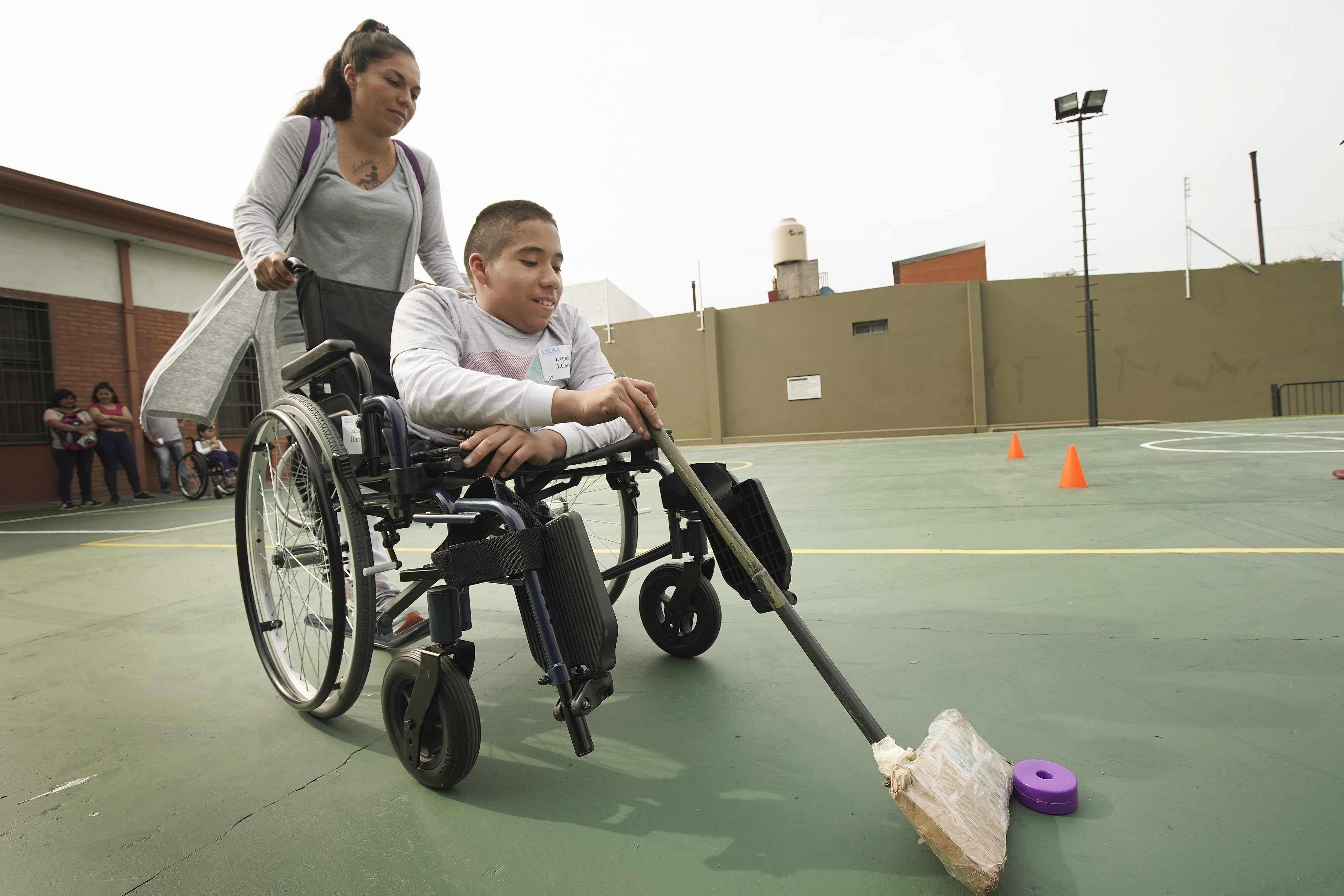 Juan Carlos Loza plays a game with the help of his mother, Paola Loza, after Latter-day Saint Charities donated a wheelchair to him at the Villa Urquiza Ward meetinghouse in Buenos Aires, Argentina, on Wednesday, Aug. 28, 2019.