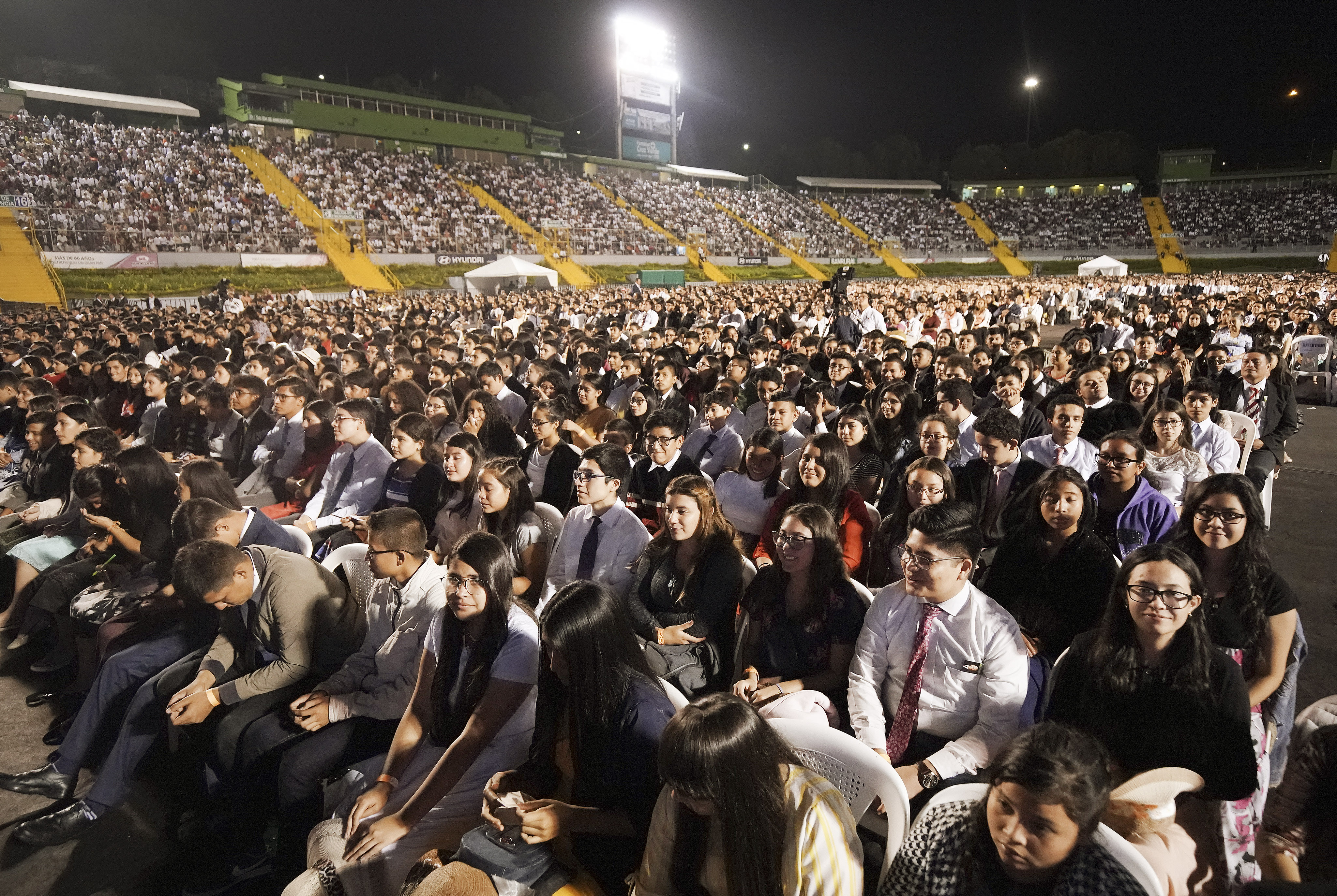 Attendees listen to President Russell M. Nelson of The Church of Jesus Christ of Latter-day Saints speak during a devotional at Estadio Cementos Progreso stadium in Guatemala City on Saturday, Aug. 24, 2019.