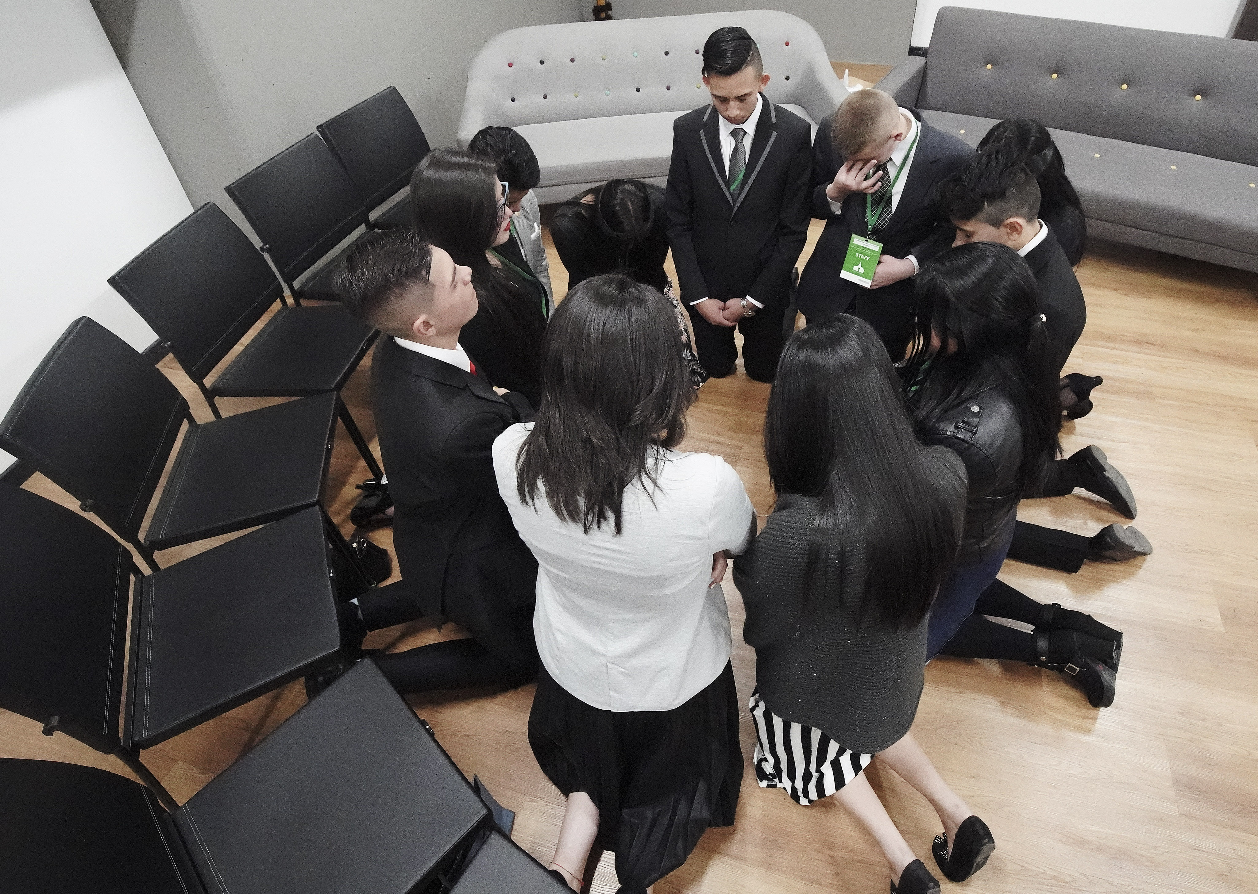 Youth attendees pray prior to meeting President Russell M. Nelson of The Church of Jesus Christ of Latter-day Saints in Bogota, Colombia, on Sunday, Aug. 25, 2019.