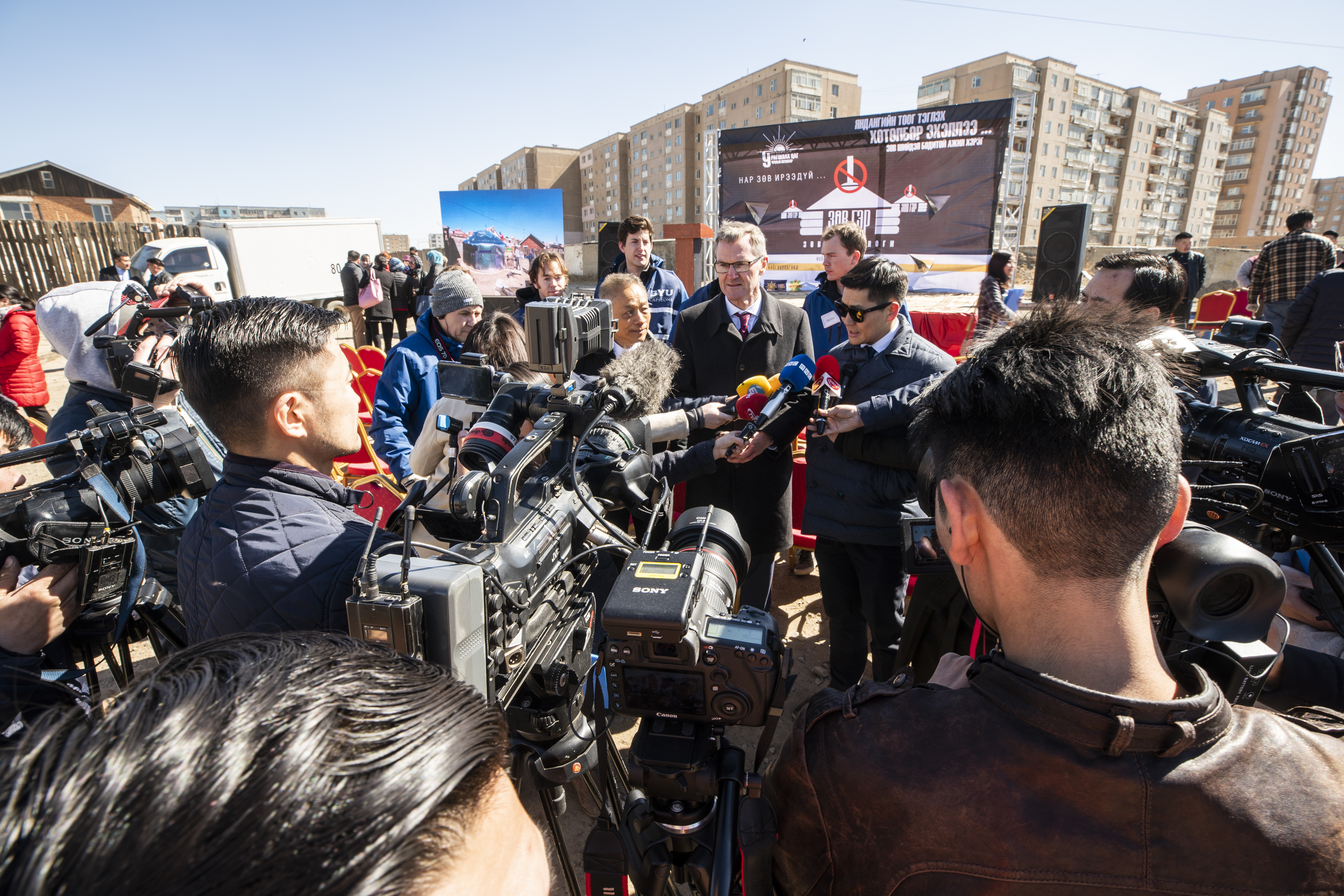 Government officials and Asia Area representatives of the Church gather before local media in Ulaanbaatar, Mongolia, during a ceremony to highlight the work of BYU Engineering Capstone teams working to implement a project of retrofitting existing gers with insulation and building a new structure to help with heat efficiency to help with pollution problem due to burning coal.