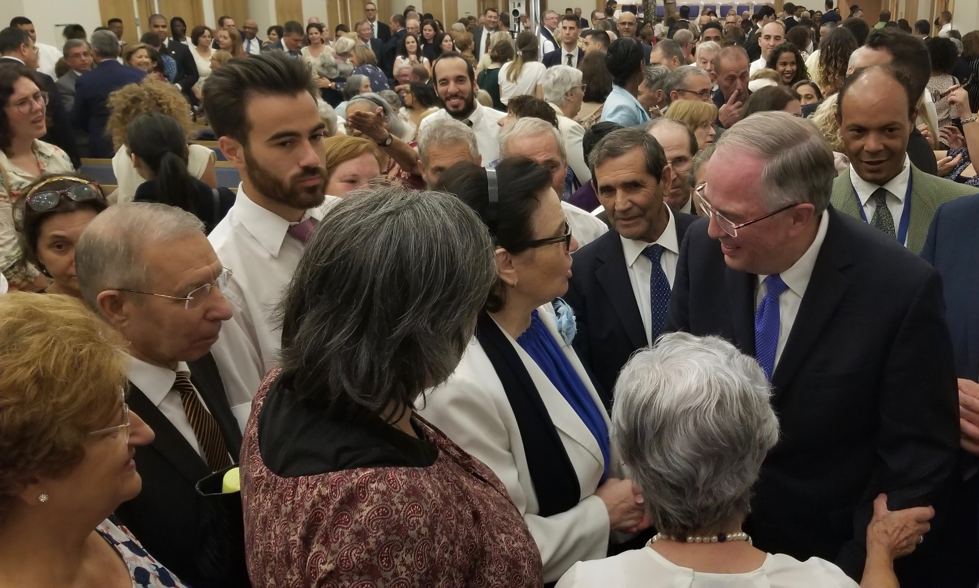 Elder Neil L. Andersen of the Quorum of the Twelve Apostles, right, greets individuals following a meeting with Portugal's pioneer Latter-day Saints on Saturday, Sept. 14, 2019, in Lisbon. The crowd of members in the meetinghouse chapel waiting to meet him is visible to his side and behind him.