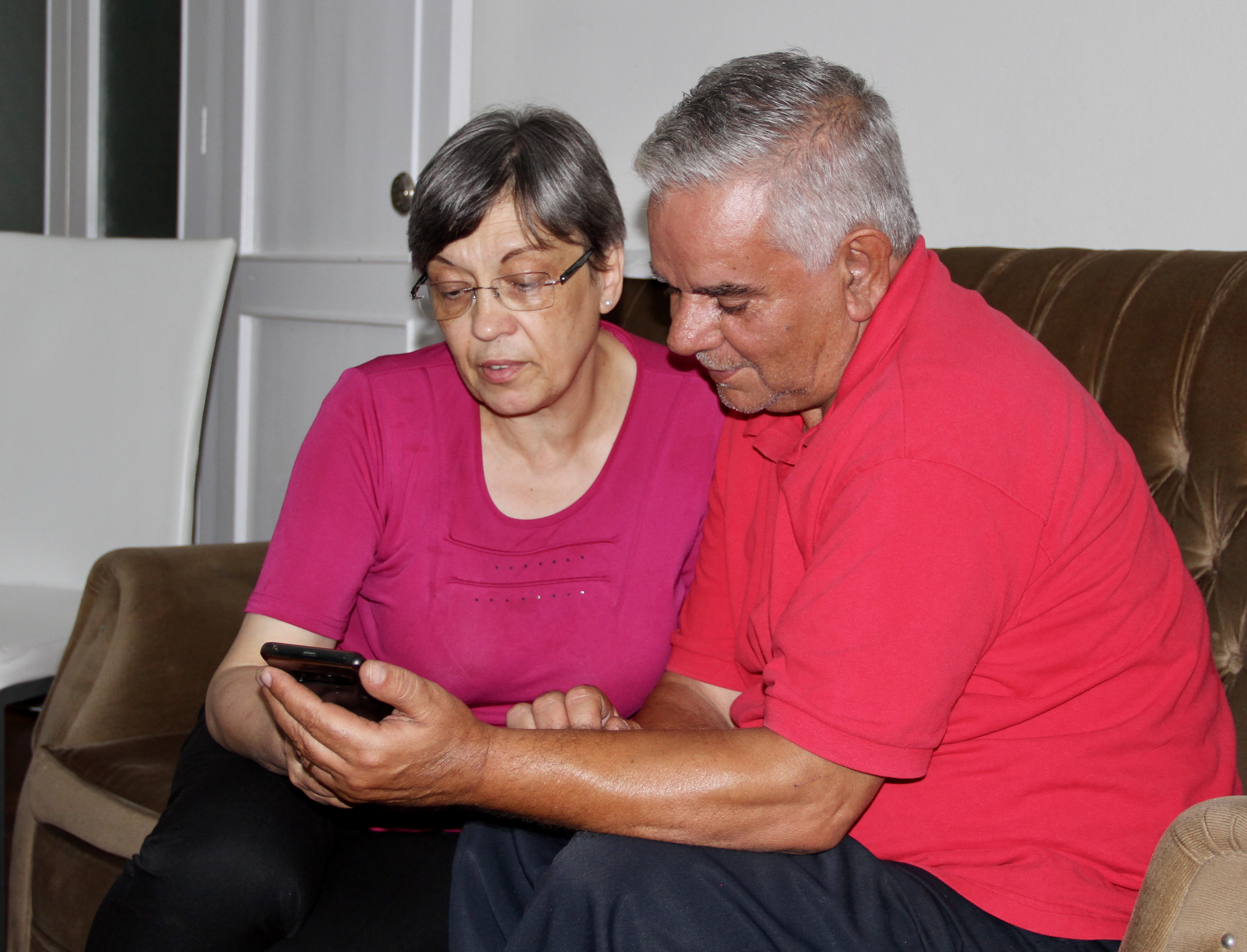 Nair Alves and Luís Alves read coverage of the Lisbon Portugal Temple dedication on a smartphone in their home in Angra, Terceira Island, Azores, on Sept. 16, 2019. The Alves have since left for Lisbon for a year-long service mission at the same temple.