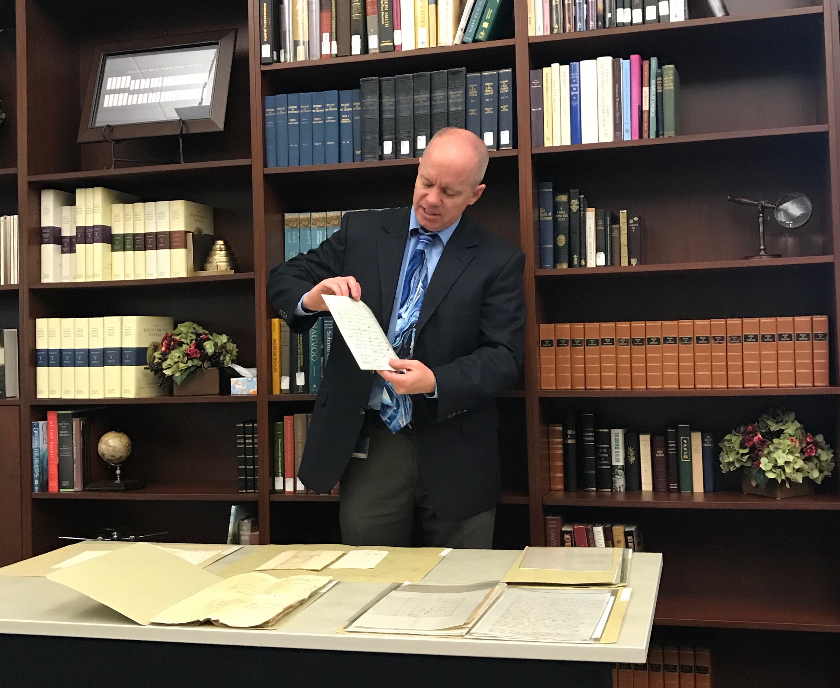 "Alex D. Smith, an editor with the Joseph Smith Papers project, shows a document from ""Documents, Vol. 9: December 1841-April 1842."""