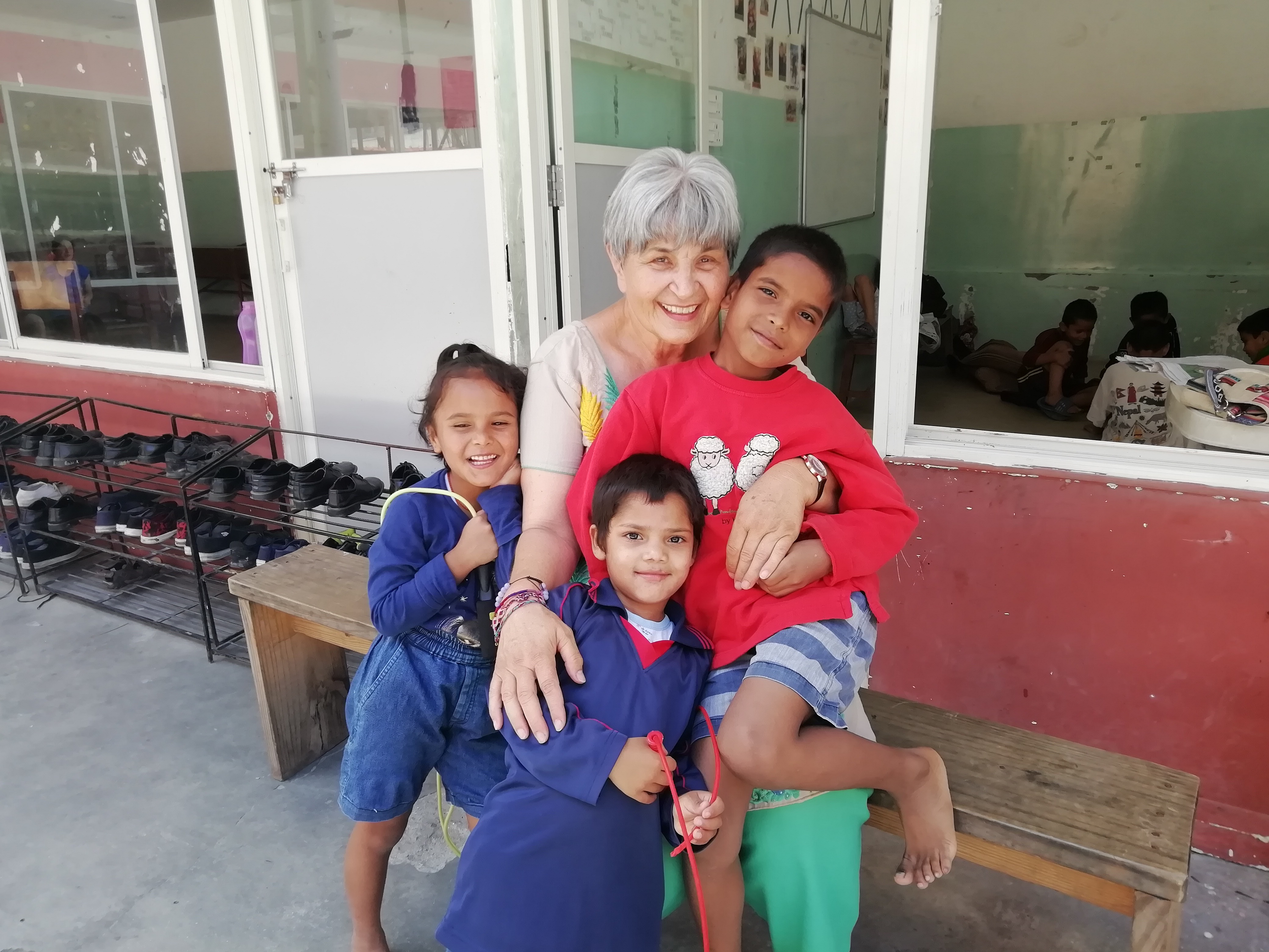 """Children from Home of Hope in Nepal spend time with their """"Aunt"""" Ellen during one of her visits in the home's courtyard in 2019. Ellen Dietrich is the founder and chairwoman of Home of Hope or Self Help Nepal as it is also known."""