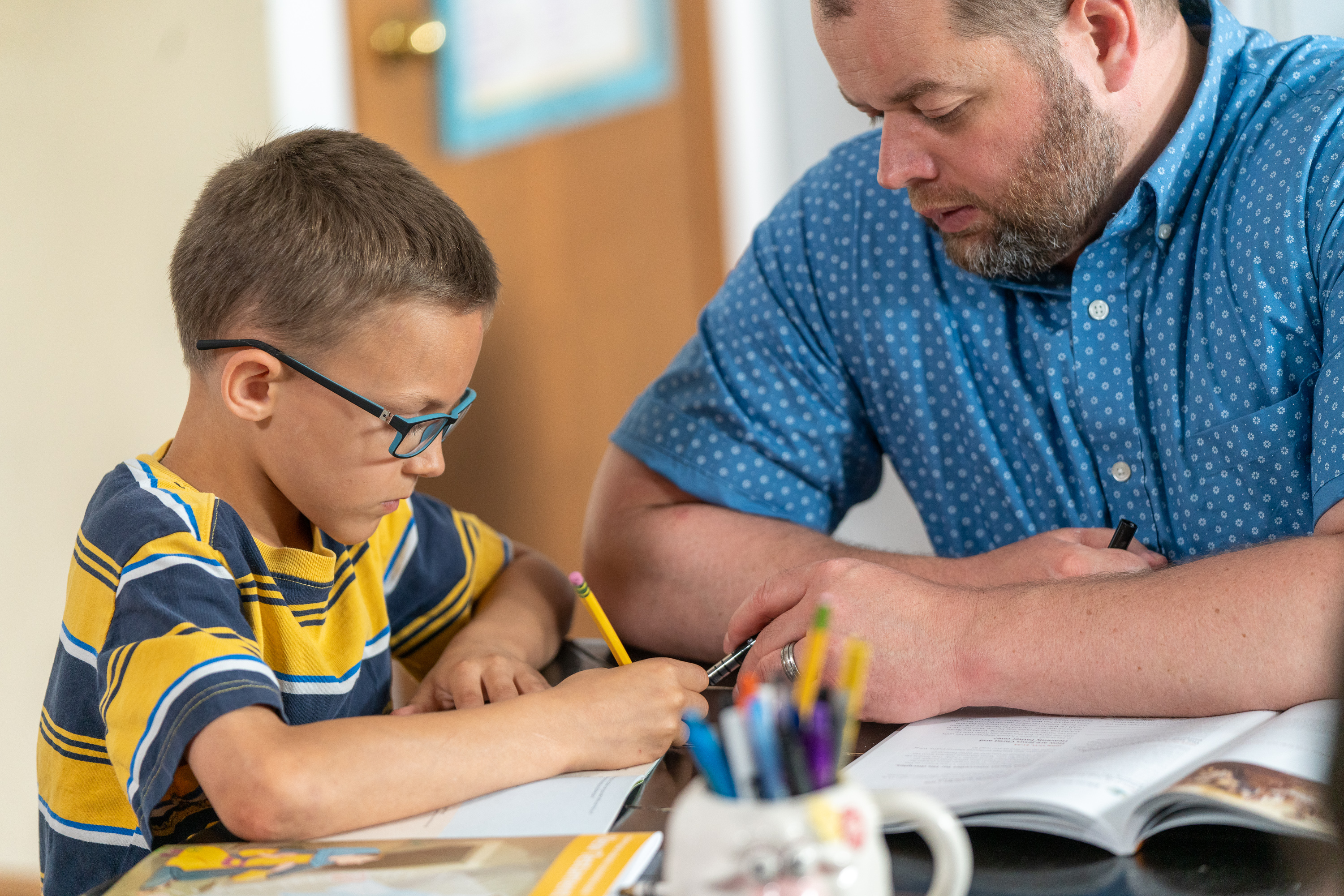 Peter, a 9-year-old from a pilot stake in Columbus, Ohio, practices reading and writing with his father. As part of the Children and Youth program, Peter set a goal to pass his reading test at school.