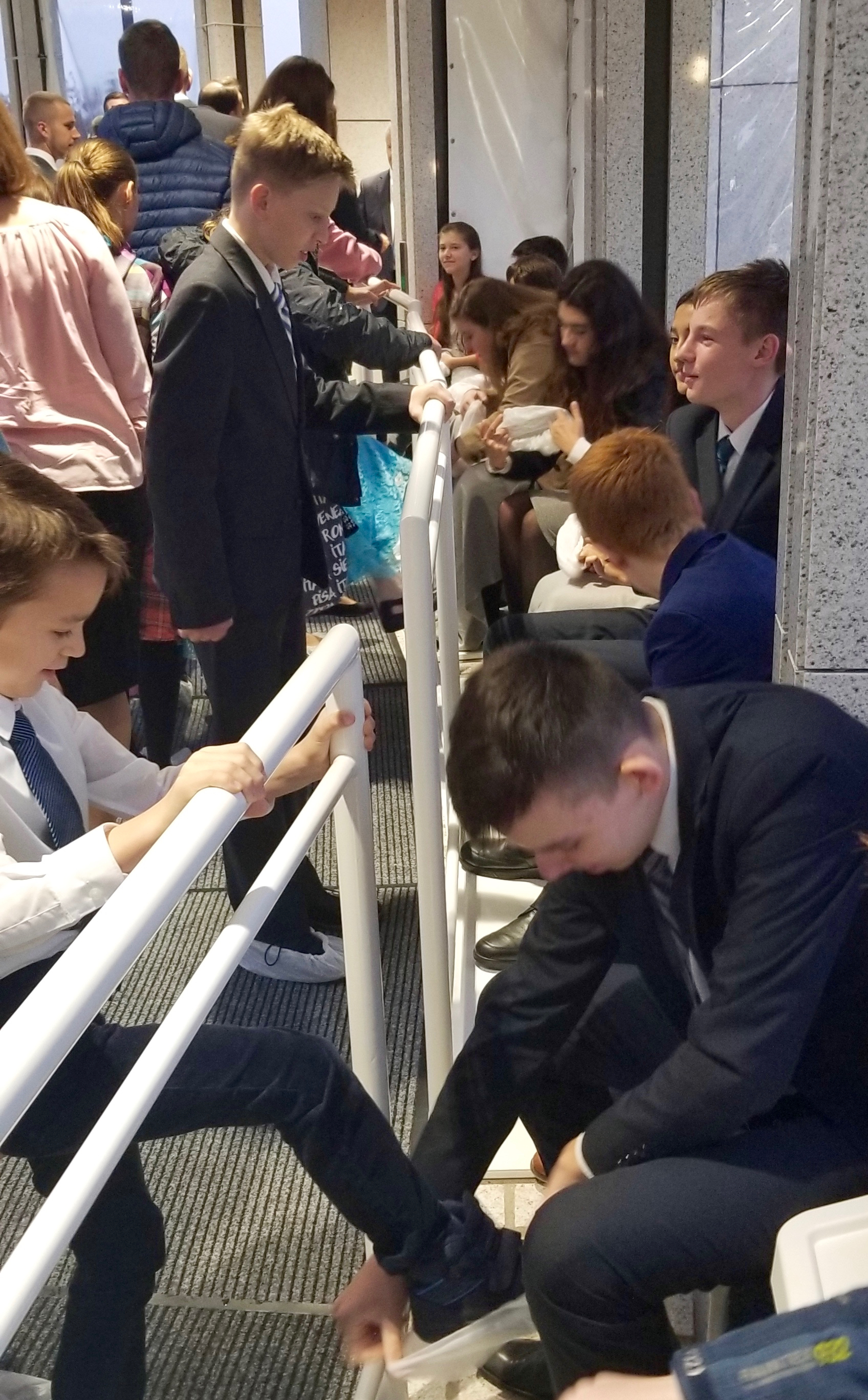 Youth help place protective coverings on the shoes of those arriving to attend the rededication services of the Frankfurt Germany Temple on Oct. 20, 2019.