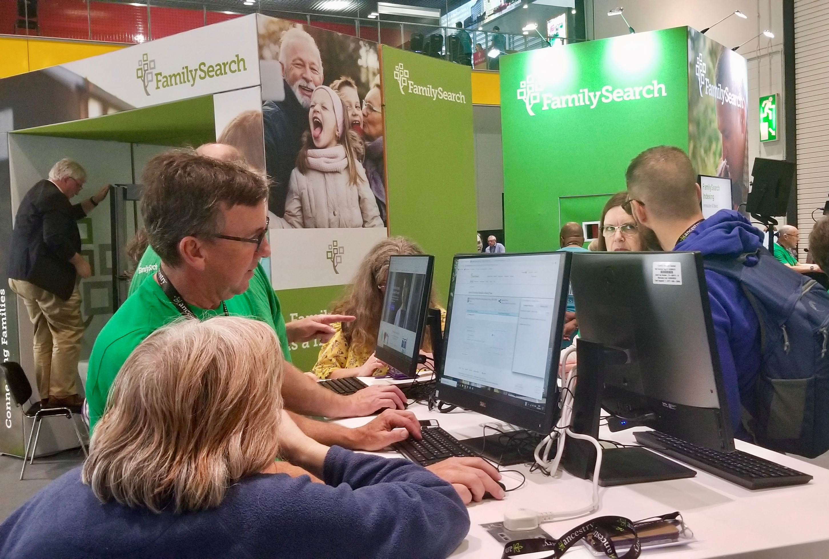 Attendees confer with staff at the FamilySearch booth in the RootsTech London exhibition area at London ExCel convention center on Thursday, Oct. 24, 2019.