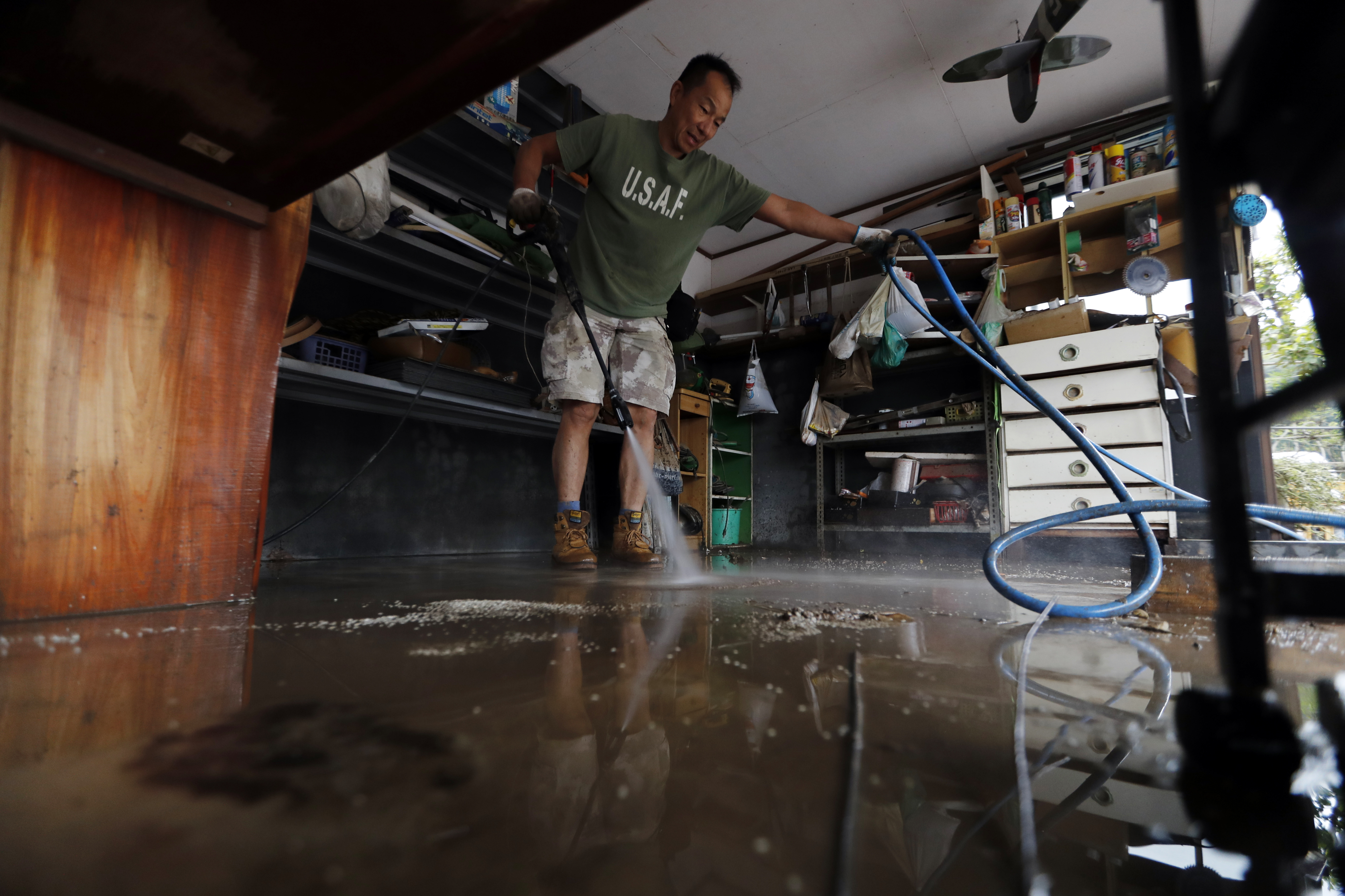 A volunteer helps clean up from Typhoon Hagibis Monday, Oct. 14, 2019, in Kawagoe City, Japan. Rescue crews in Japan dug through mudslides and searched near swollen rivers Monday as they looked for those missing from Hagibis that left as dozens dead and caused serious damage in central and northern Japan. (AP Photo/Eugene Hoshiko)
