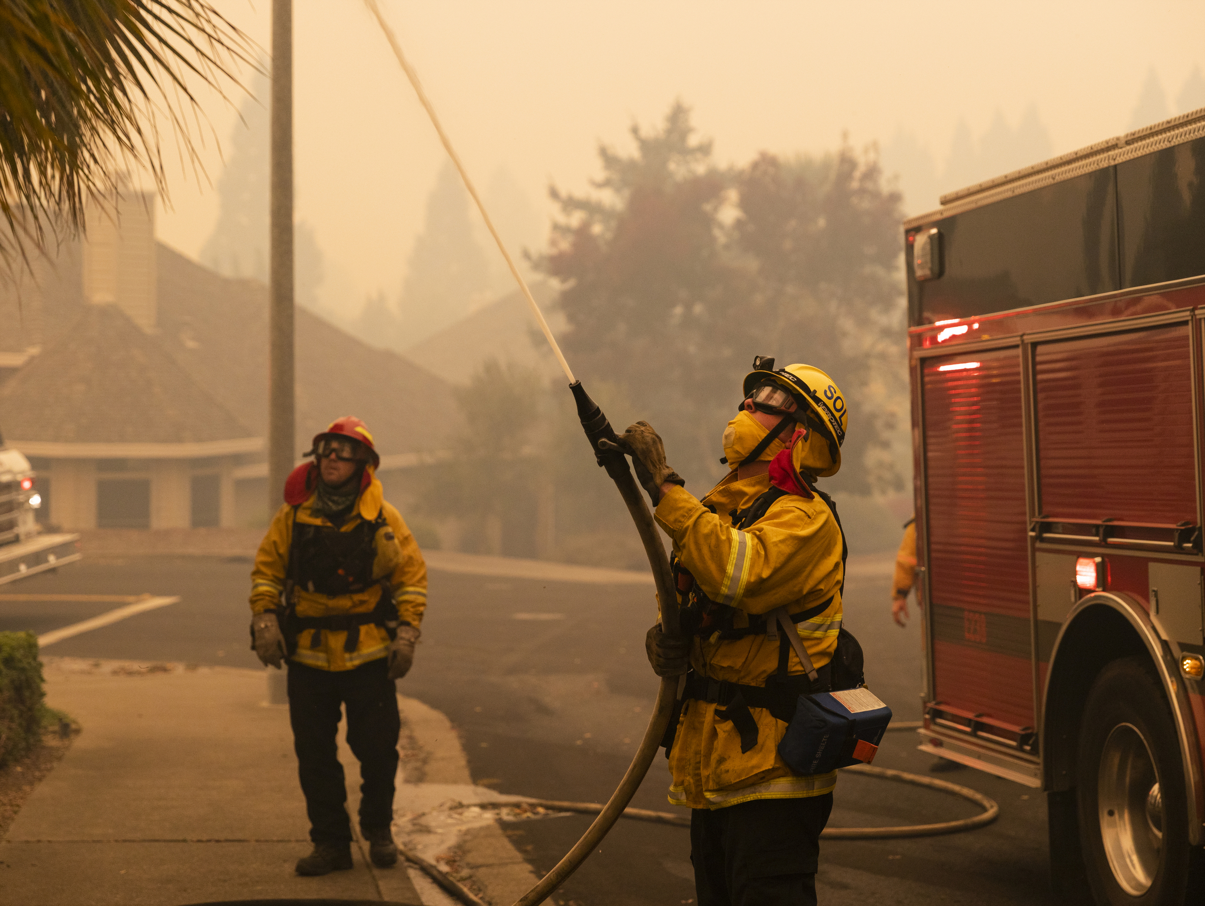 A firefighter sprays water toward trees as crews work to control the Kincade Fire on Vinecrest Road in Windsor, Calif., on Sunday, Oct. 27, 2019. (AP Photo/Ethan Swope)